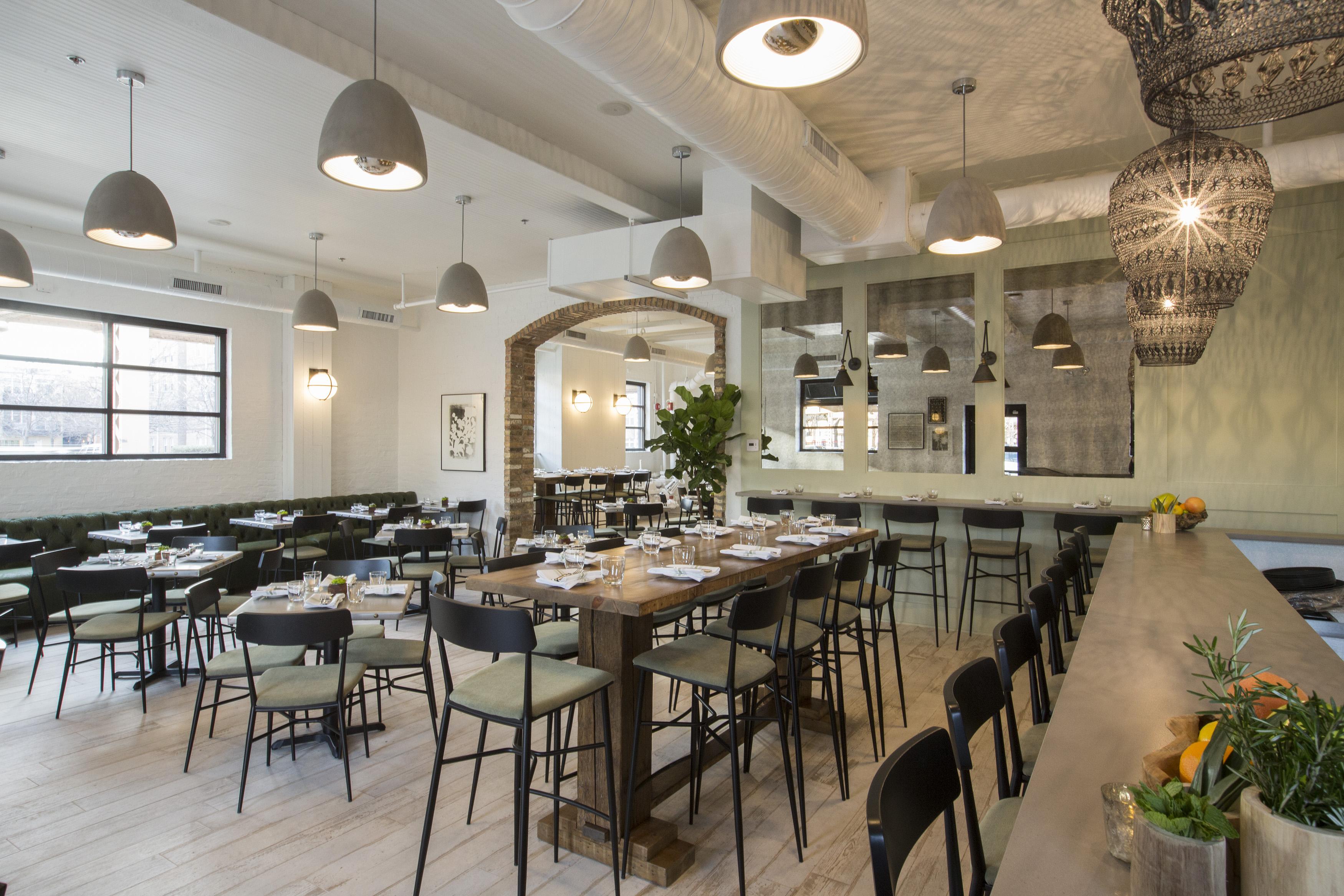 一间餐厅的用餐室,带灯光和许多桌子。