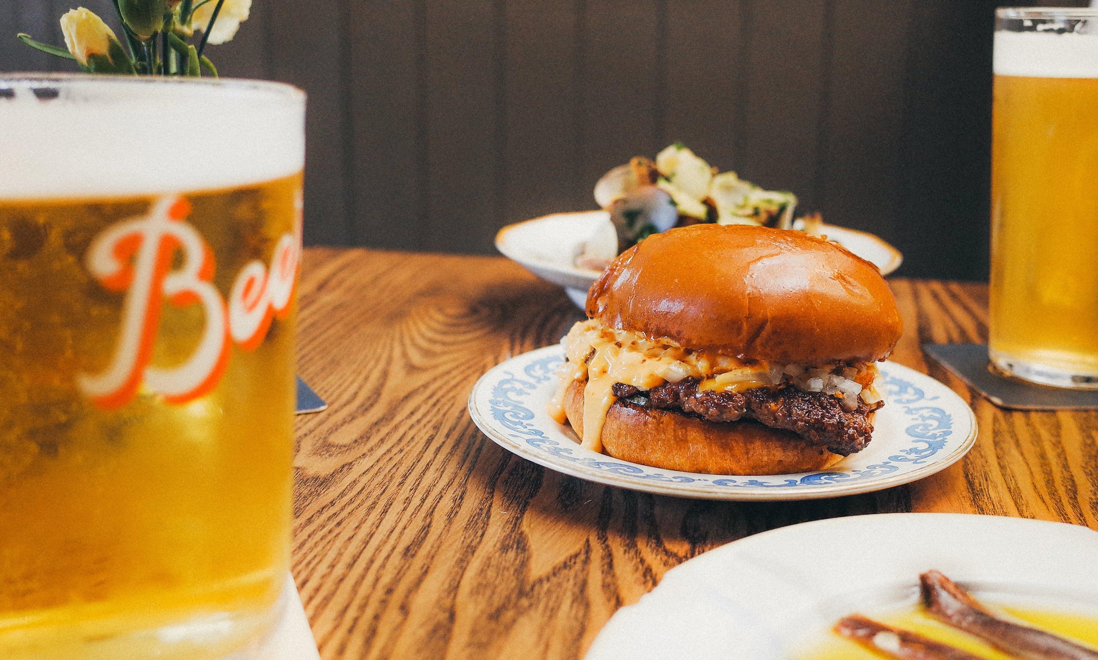 蓝花镶边的盘子上放着一个芝士汉堡,木桌上放着几品脱啤酒