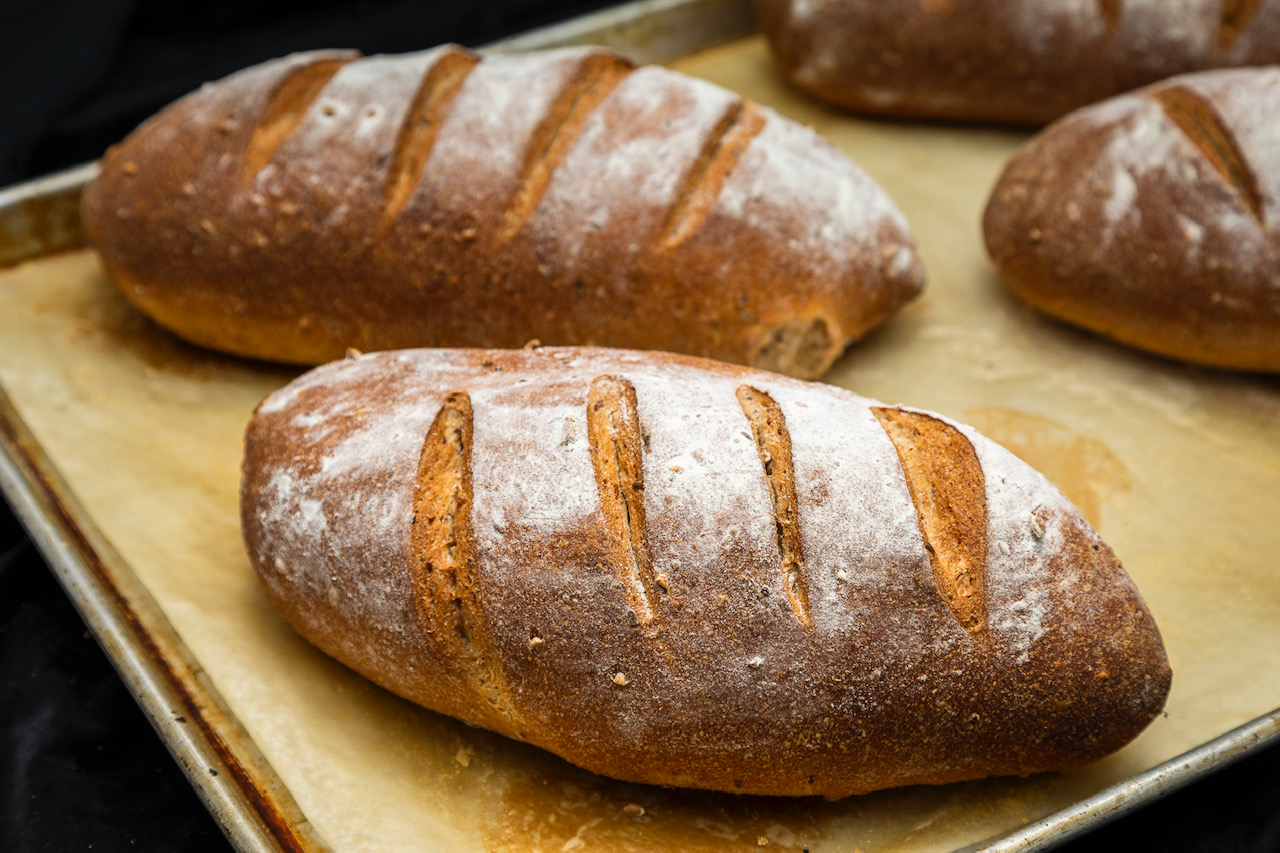 Two fresh-baked loaves of multi-grain bread dusted with flour and scored on top