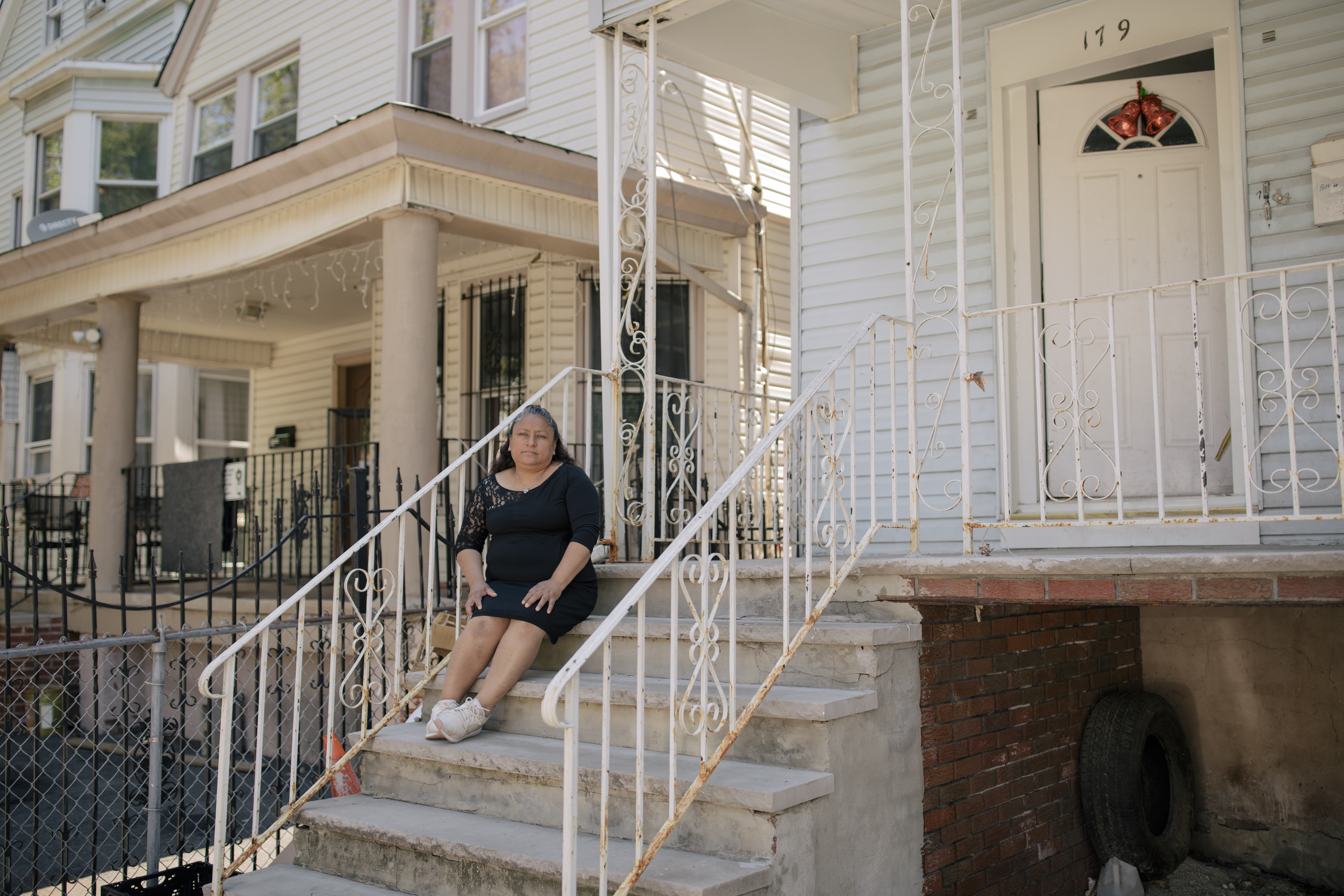 Patricia Coyotecatl, wearing a black dress and white sneakers, sits on the concrete front steps of her home in Newark, which is framed by a white metal fence on either side.