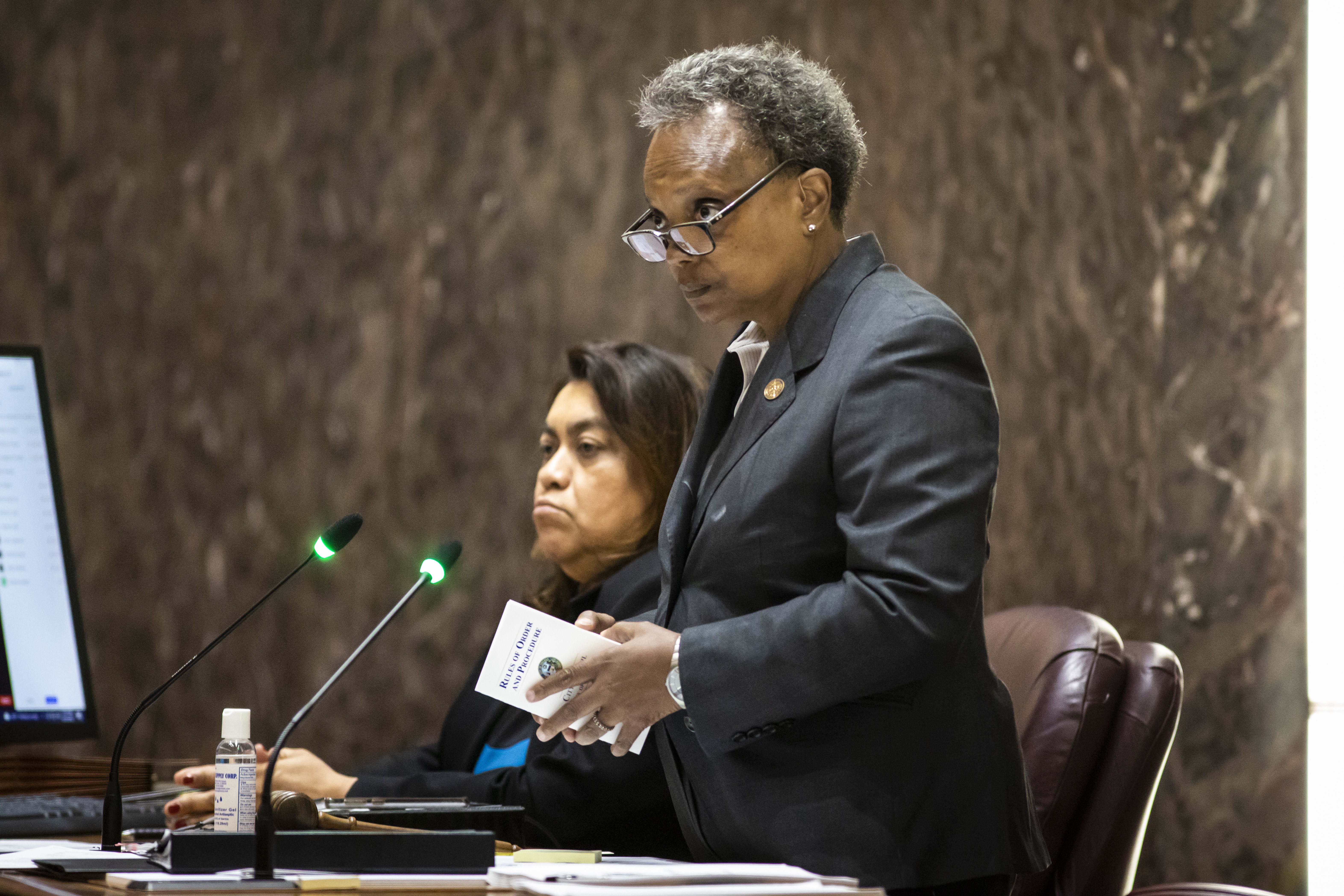 """Mayor Lori Lightfoot presiding at Wednesday's Chicago City Council meeting. In her hands, she's holding a booklet of the Council's """"Rules of Order and Procedure"""" — rules she too often flouts, according to 22 aldermen who sent her a letter of complaint on Thursday, a day after a Council meeting adjourned abruptly, leaving some major business unfinished."""