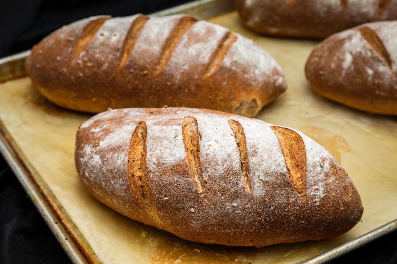 两块刚烤好的杂粮面包,上面撒满了面粉,上面有划痕