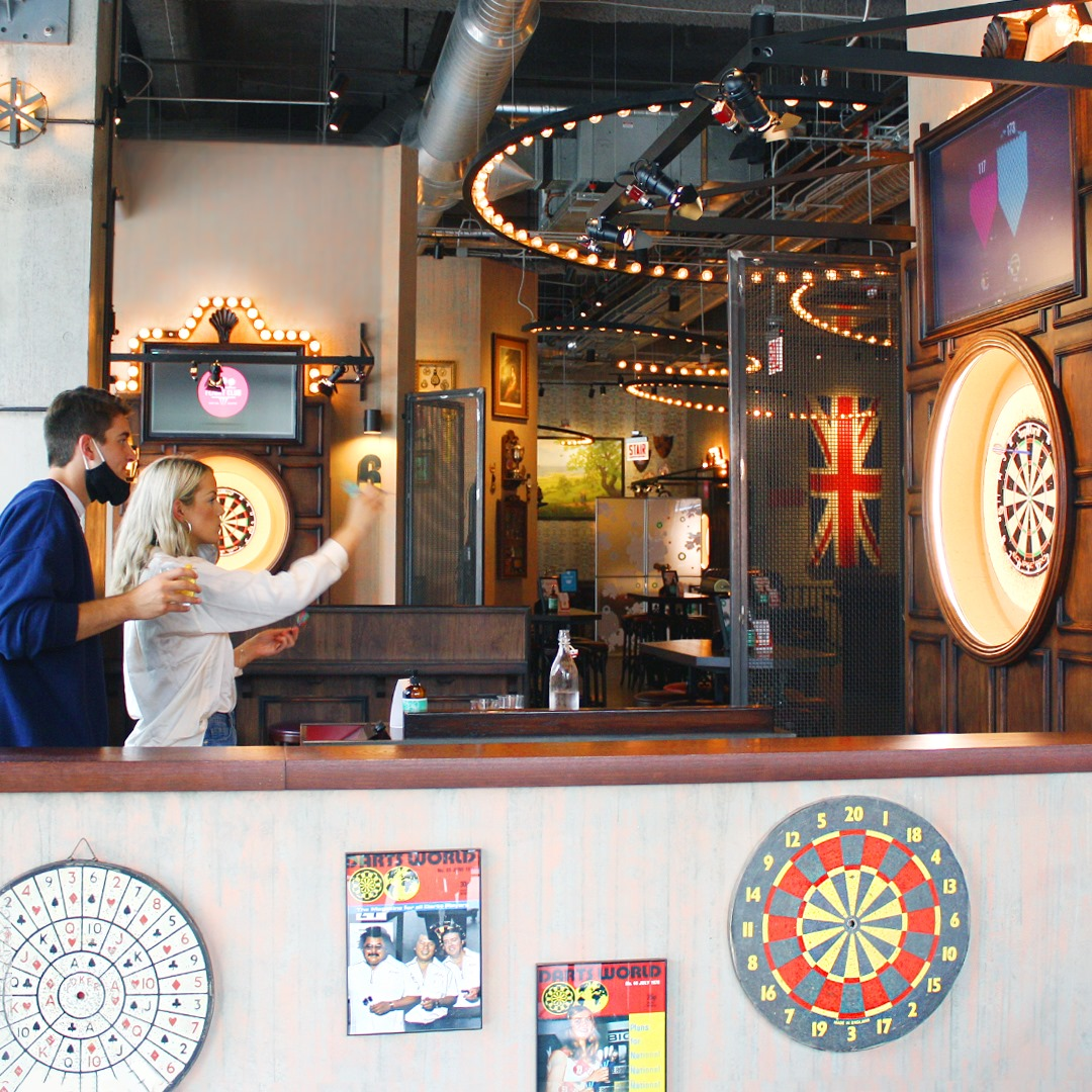 two people playing darts in a bar