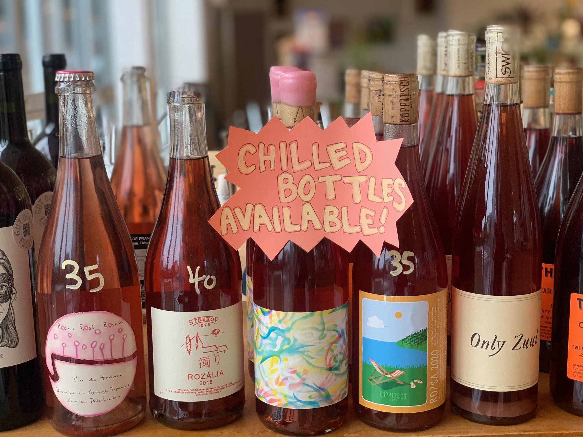 """A sign attached to a group of red and pink bottles of wine reads, """"Chilled bottles available!"""""""