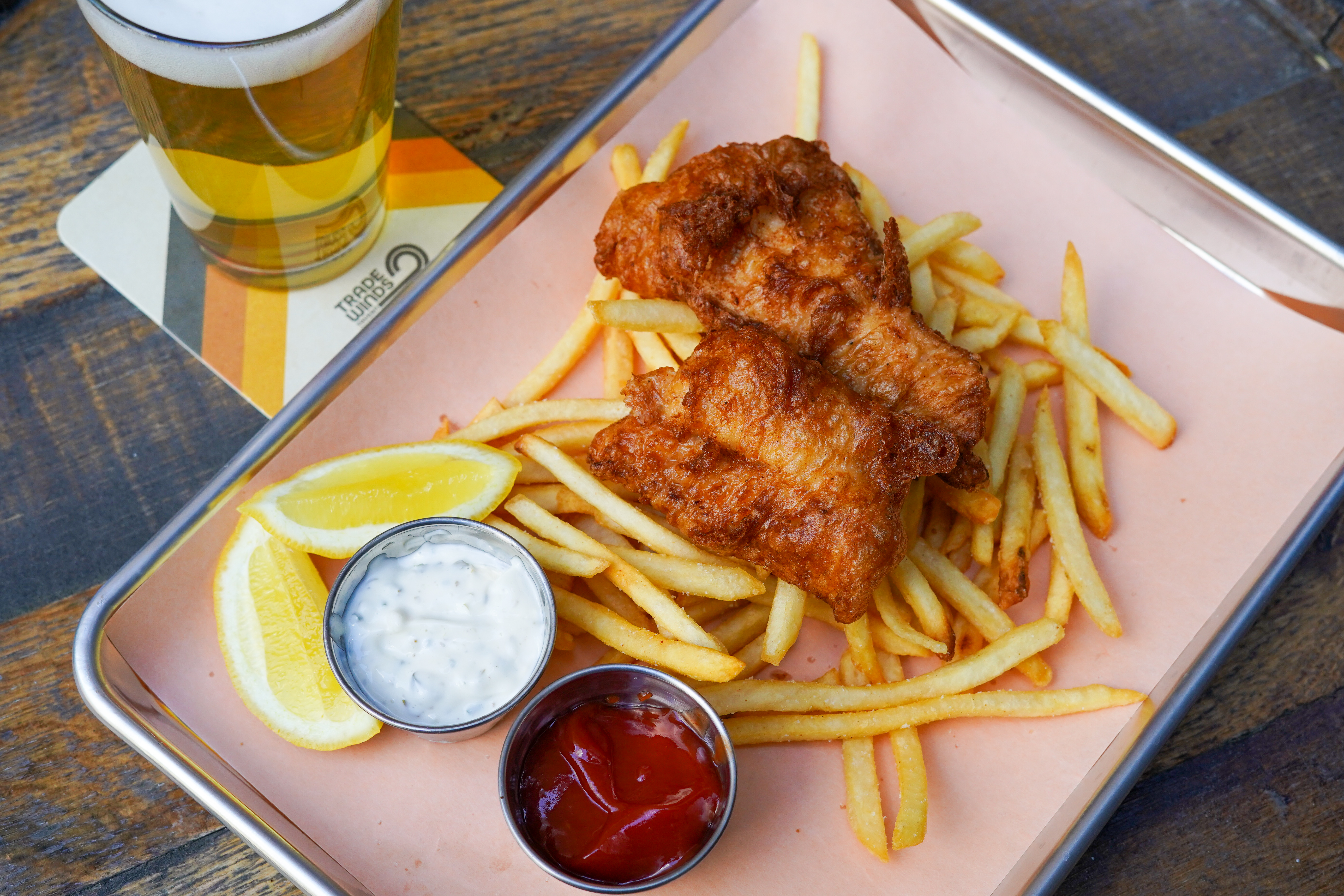 """A top-down view of fried fish with skinny fries, and a beer on a coaster that says """"Trade Winds Tavern"""" with a retro logo"""