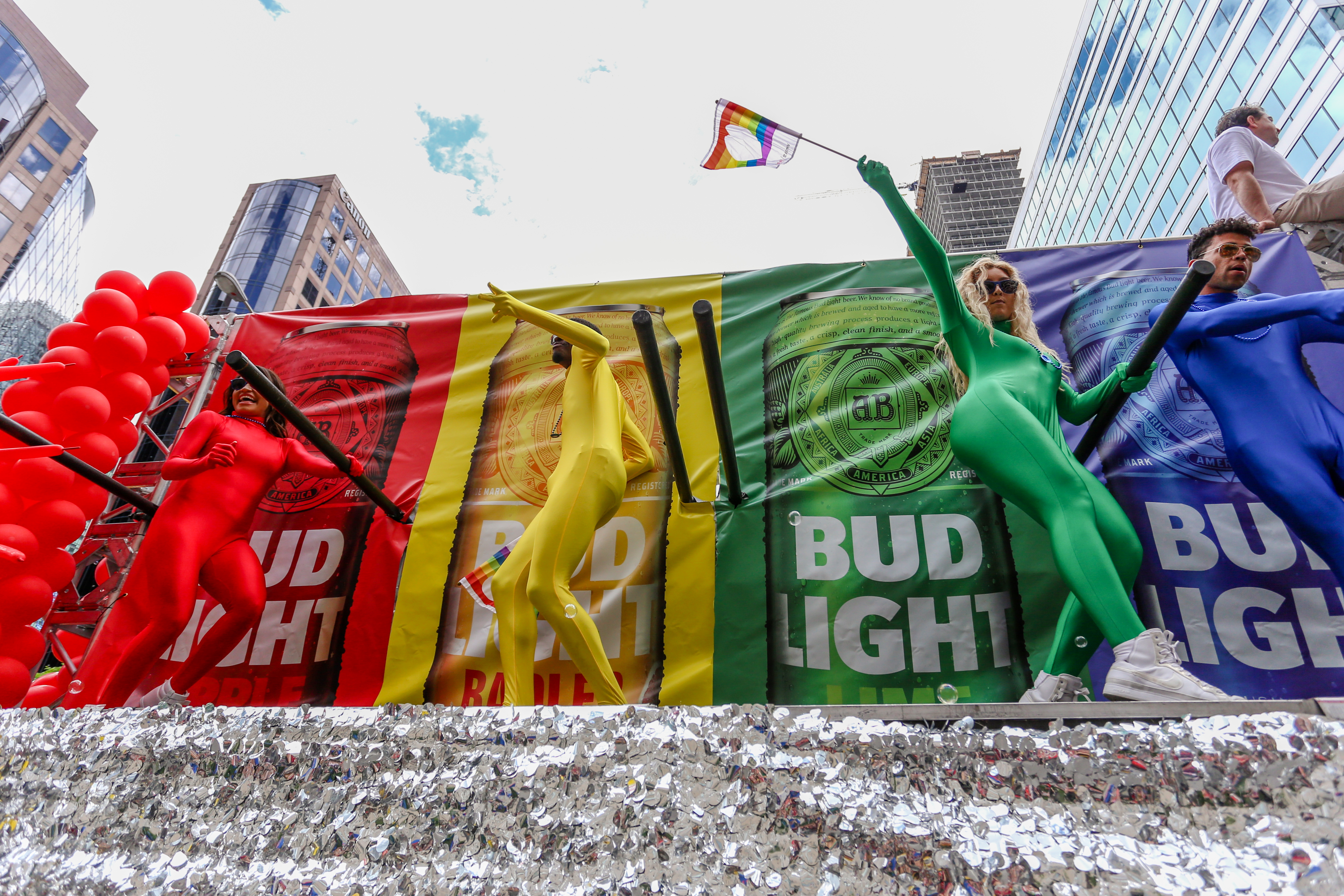 Young people in colorful lycra onesies dance on a rainbow Bud Light float at a Pride parade.