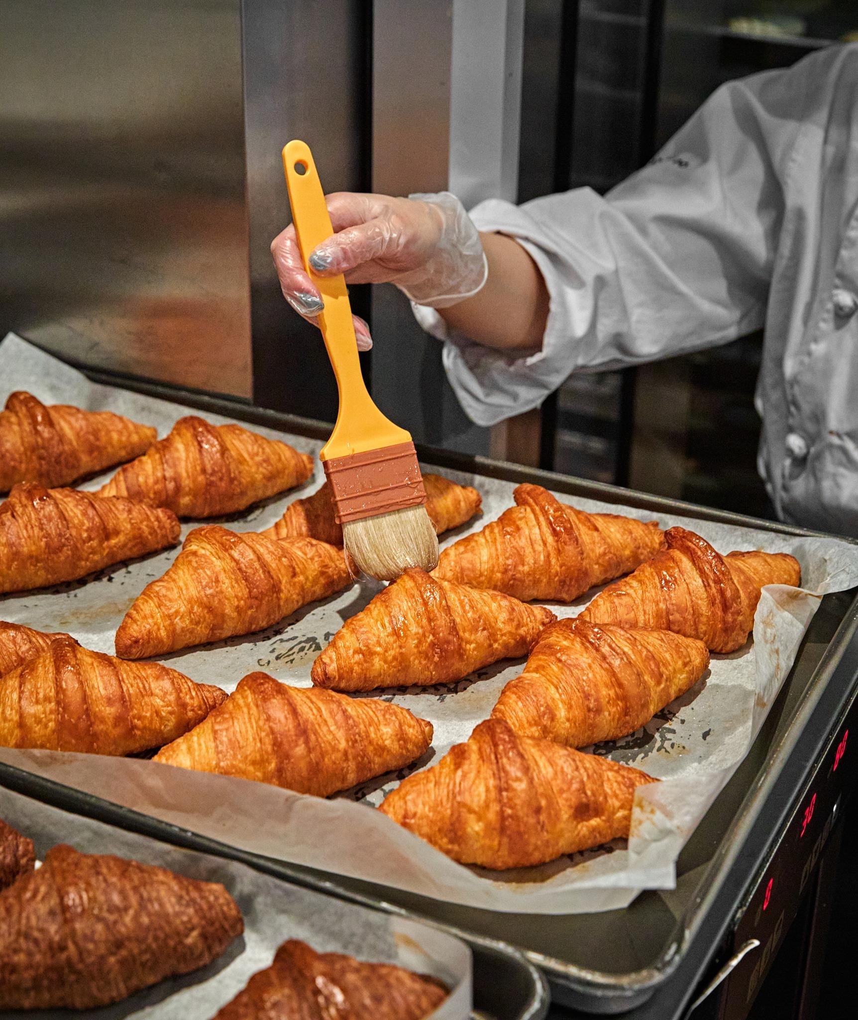 someone brushing croissants on a sheet pan