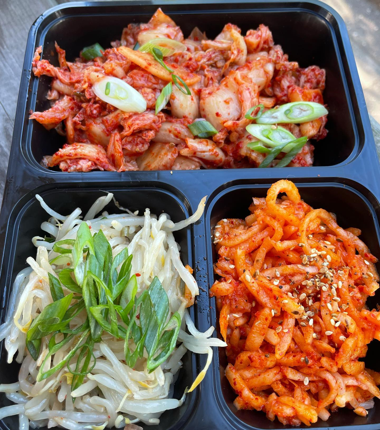 A takeout container filled with kimchi and marinated meats.