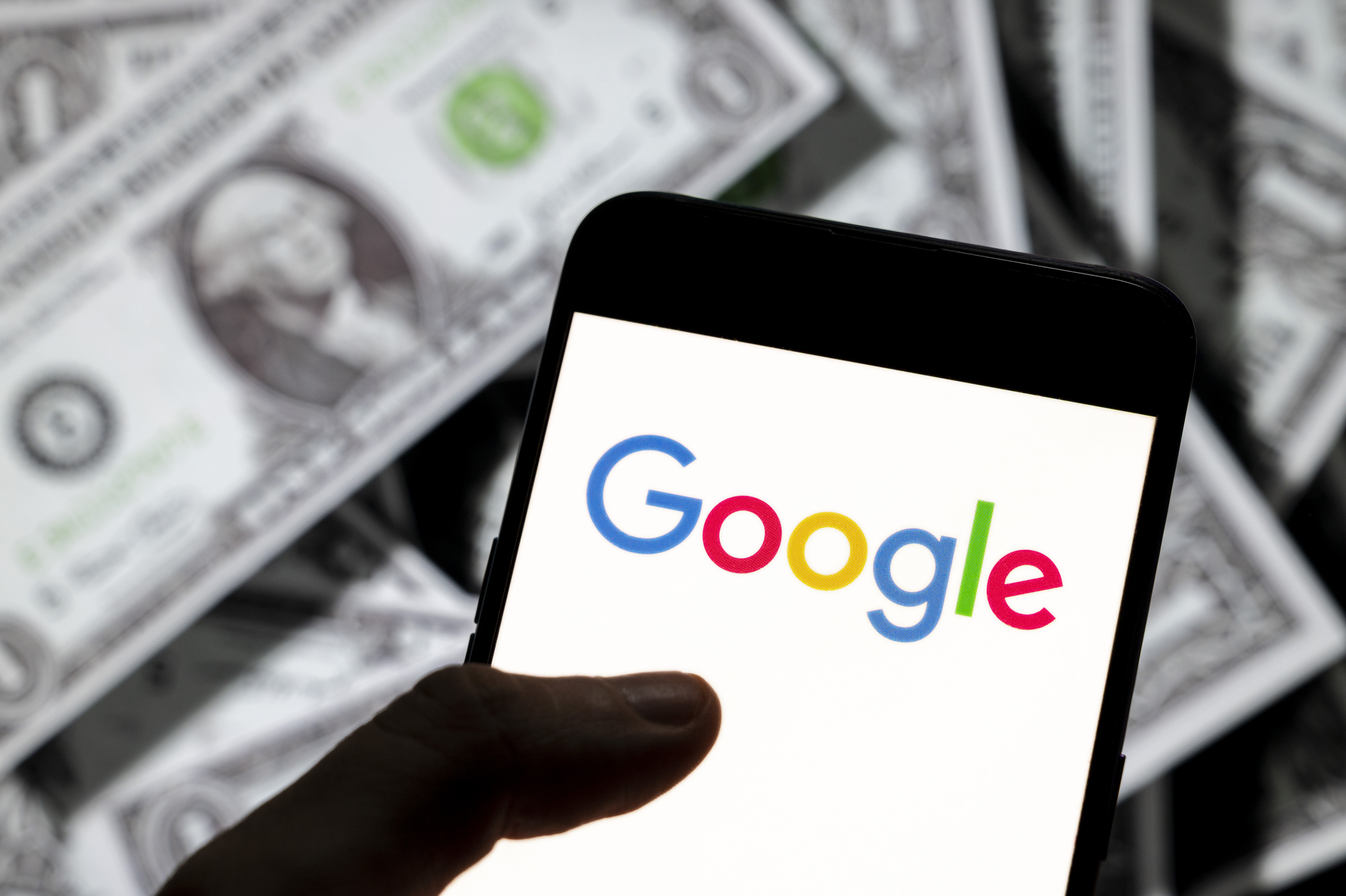 A photo illustration shows a pile of dollar bills behind a hand holding a smartphone screen displaying the Google logo.
