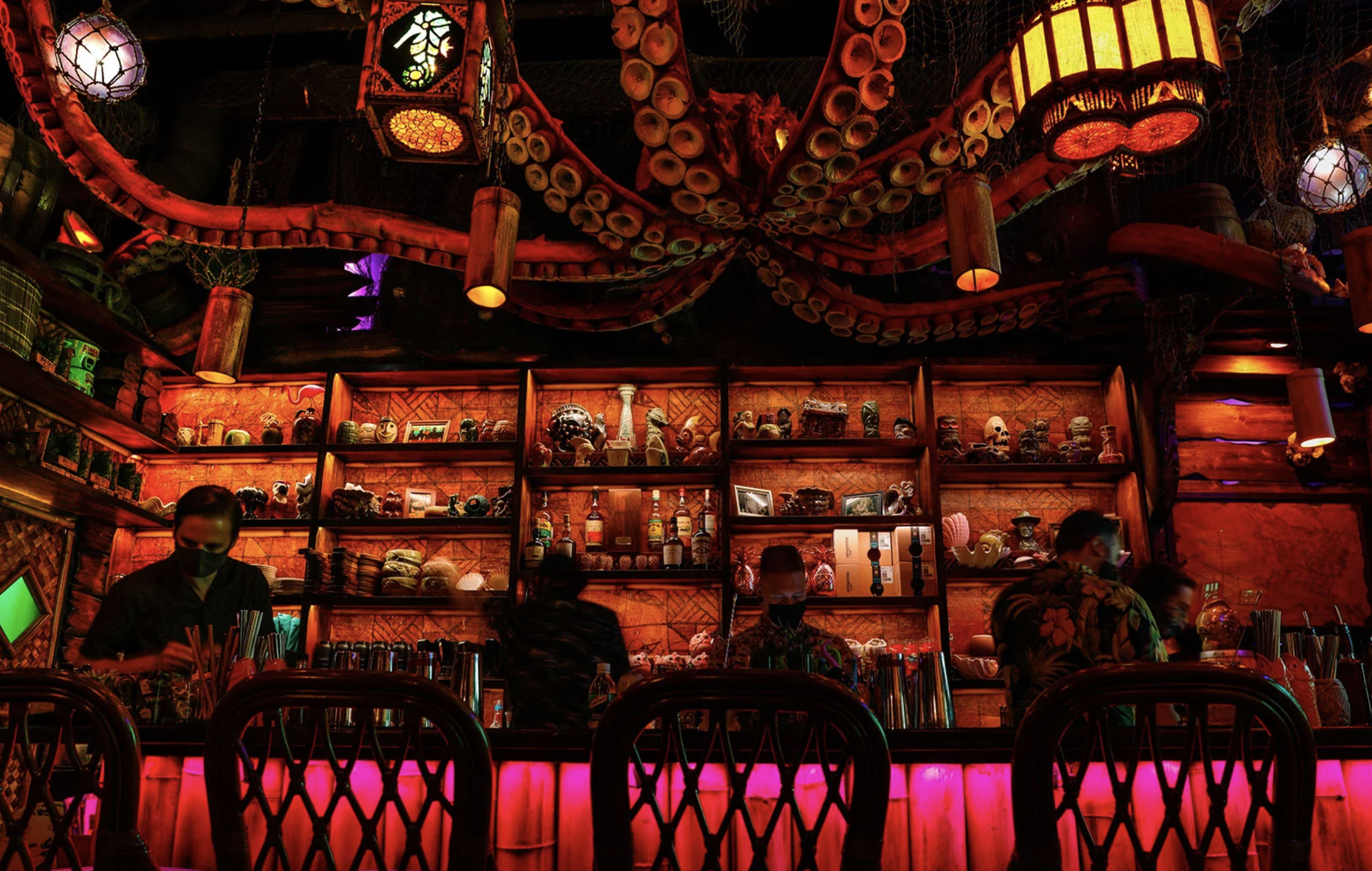 The low-lit interior of Capitol Hill bar Inside Passage, with four masked bartenders behind the bar; a giant tentacled octopus is hanging from the ceiling; in the background is a display case with a variety of intricately decorated mugs