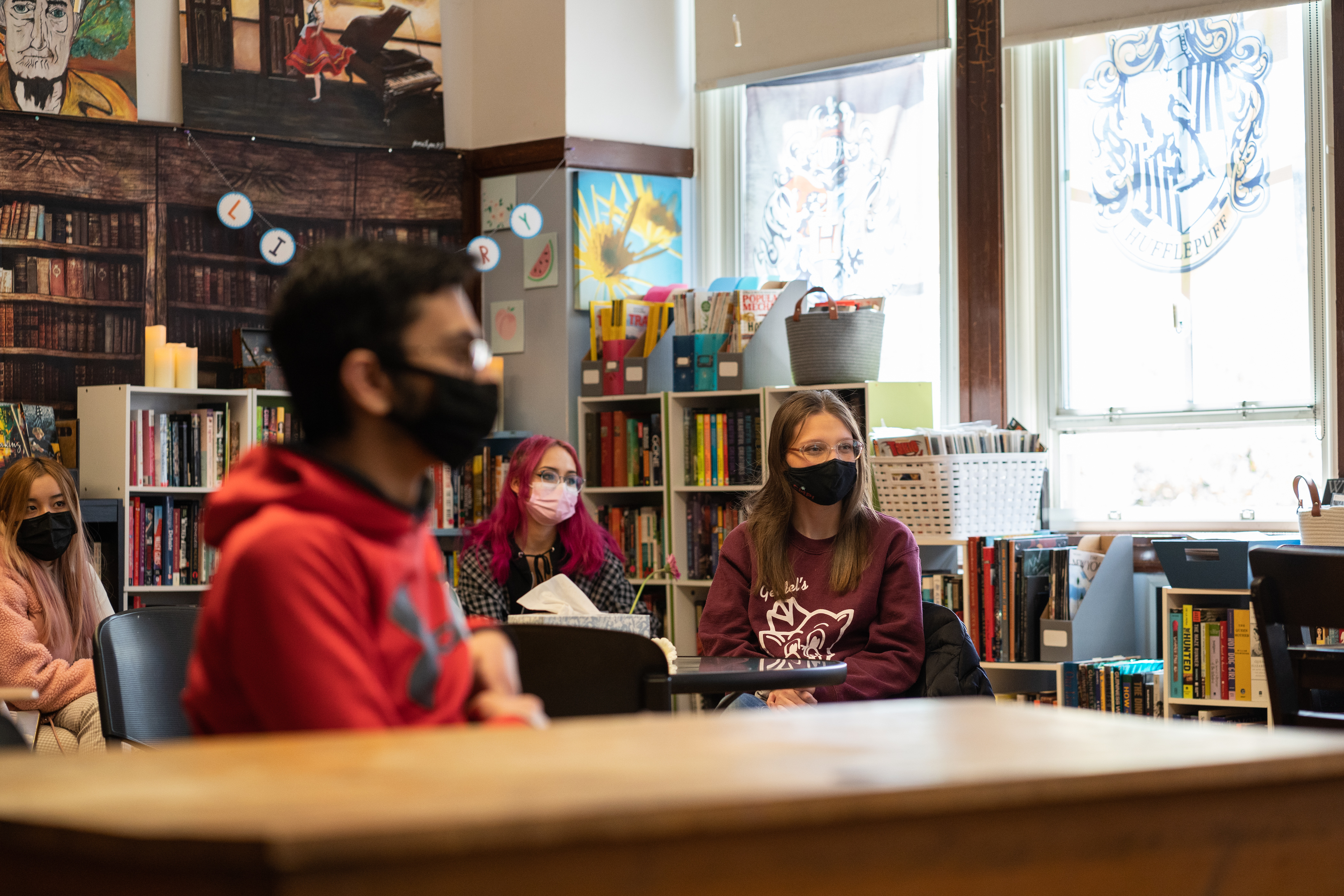 Students discuss plans in class, sitting in distanced desks wearing protective masks.
