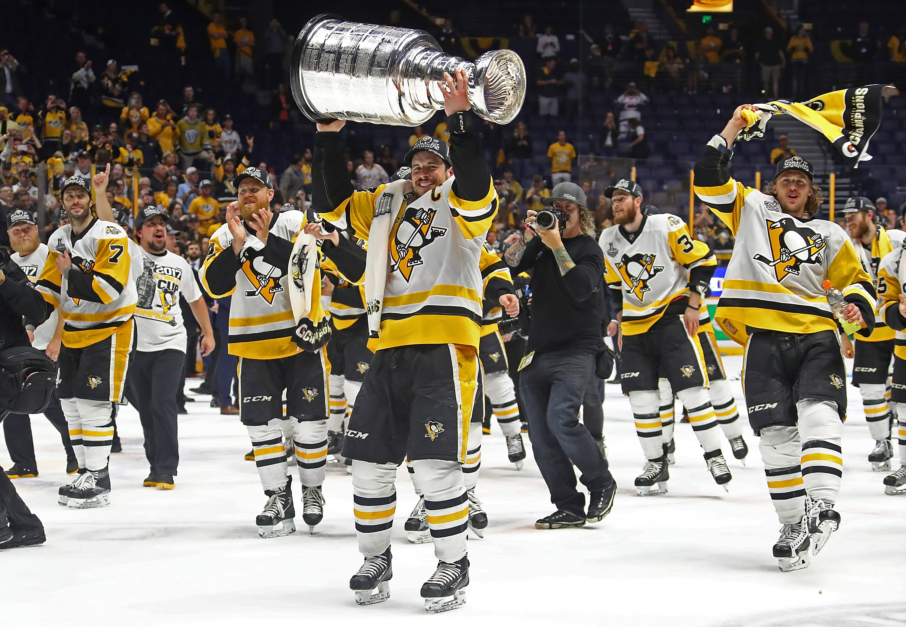 Sidney Crosby #87 of the Pittsburgh Penguins and his teammates celebrate with the Stanley Cup trophy after defeating the Nashville Predators 2-0 in Game Six of the 2017 NHL Stanley Cup Final at the Bridgestone Arena on June 11, 2017 in Nashville, Tennessee.