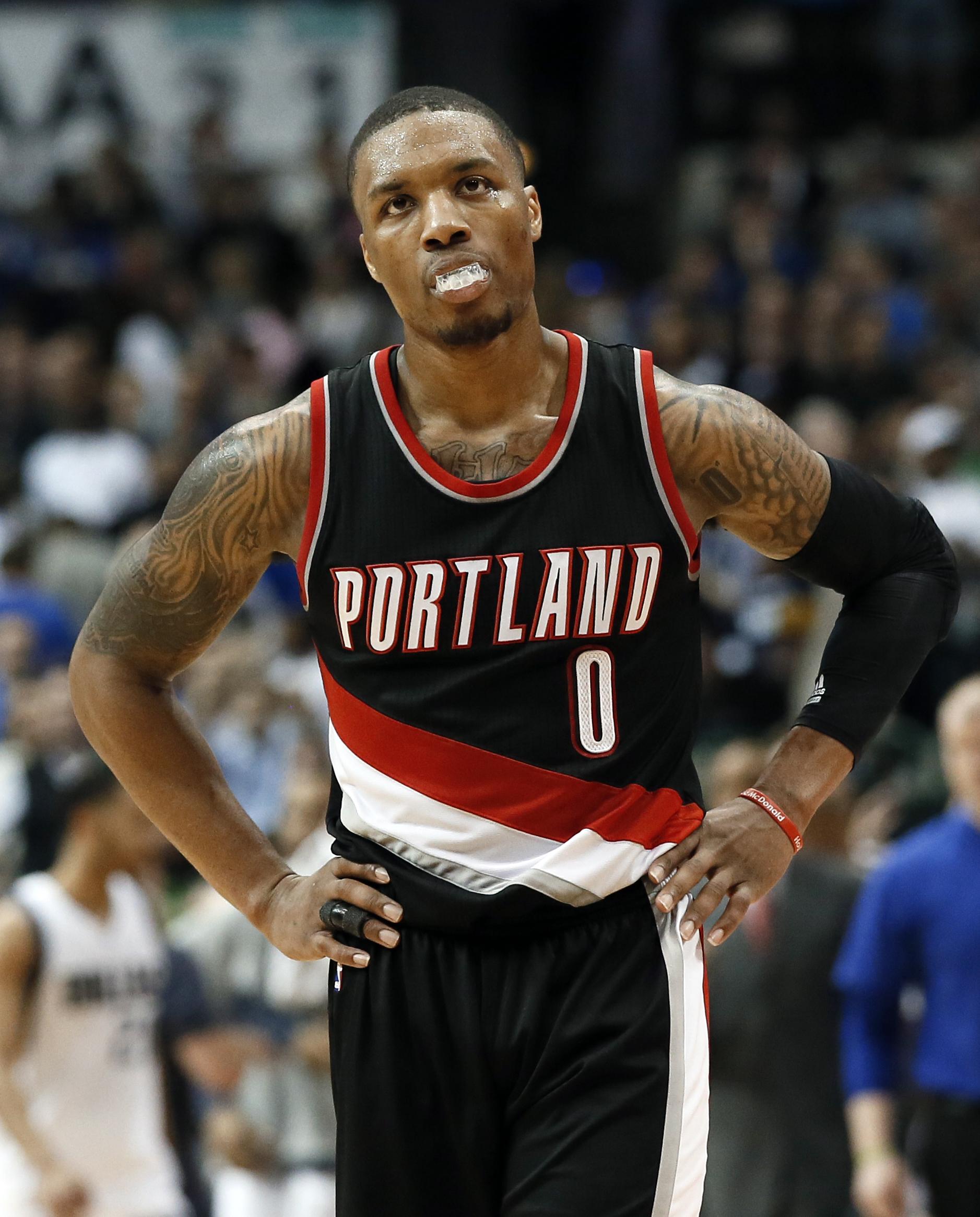 Portland Trail Blazers' Damian Lillard (0) walks back to the bench