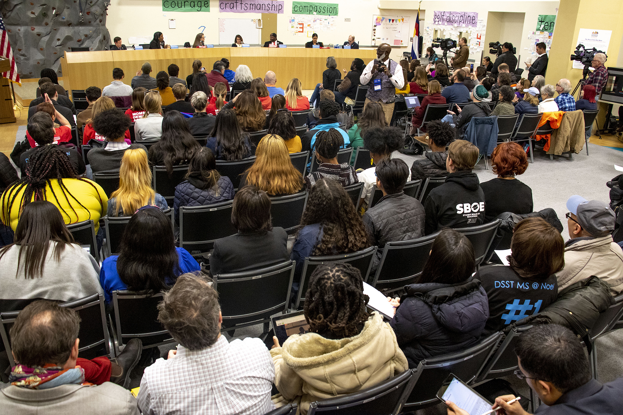 People seated in folding chairs listen to a school board meeting in a gymnasium.