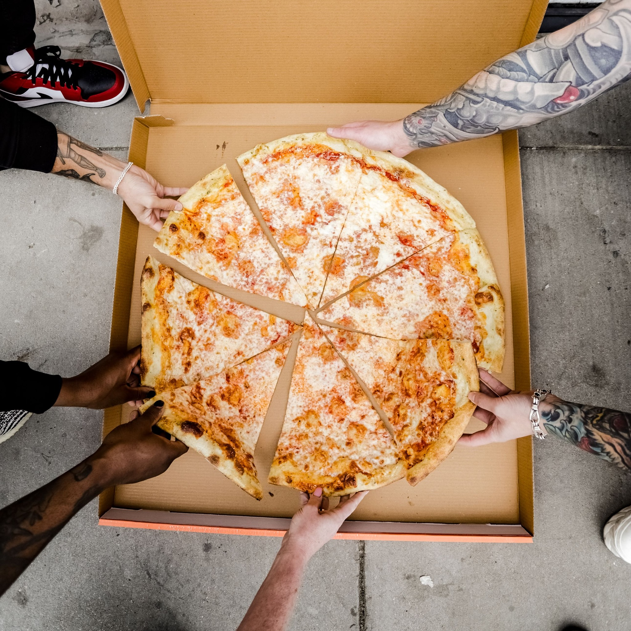 a large pizza, with several hands reaching for slices