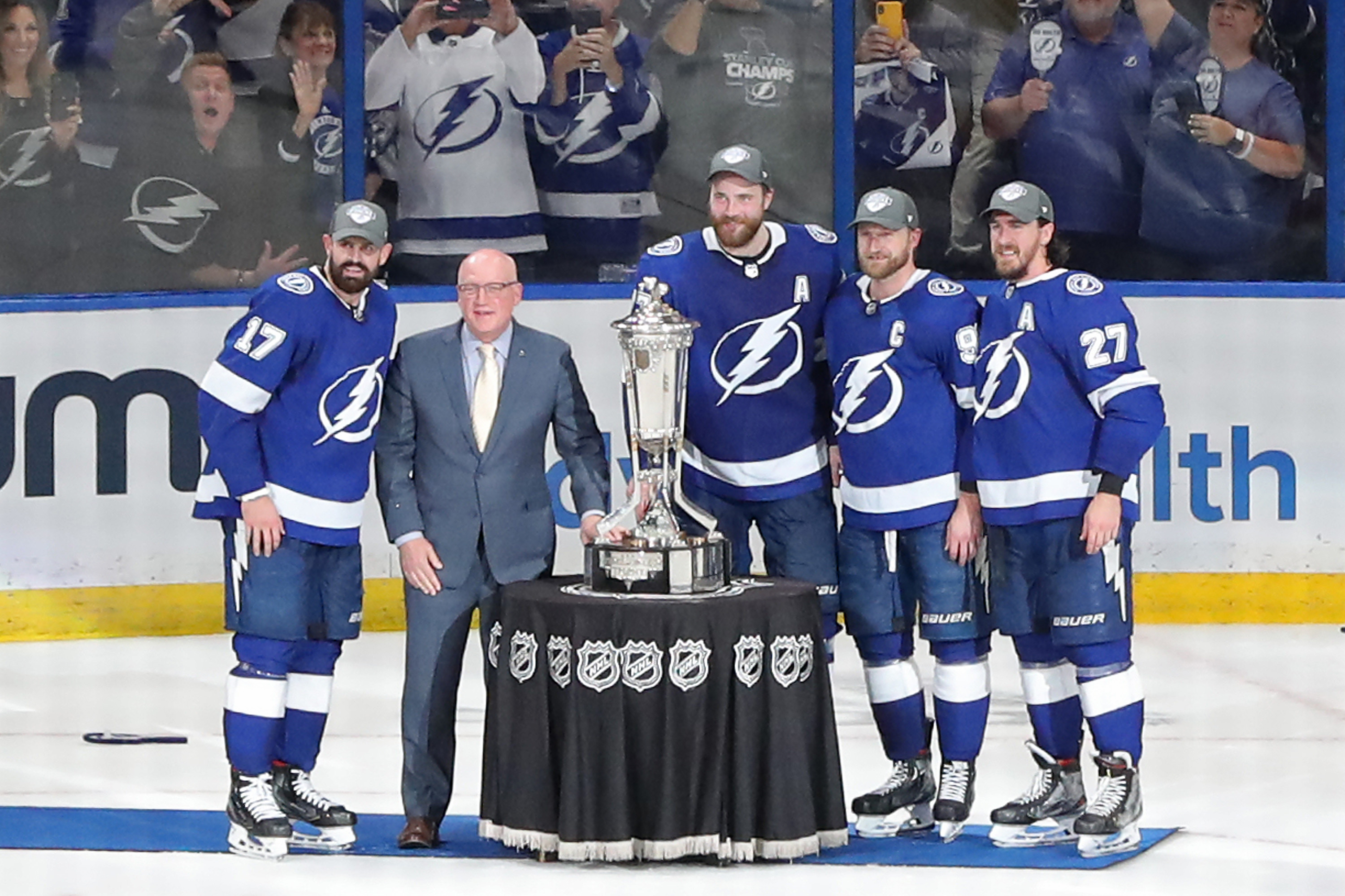 NHL deputy commissioner Bill Daly presents Alex Killorn, Ryan McDonagh, Victor Hedman and Steven Stamkos of the Tampa Bay Lightning with the Prince of Wales Trophy after defeating the New York Islanders 1-0 in Game Seven of the NHL Stanley Cup Semifinals during the 2021 NHL Stanley Cup Finals at Amalie Arena on June 25, 2021 in Tampa, Florida.