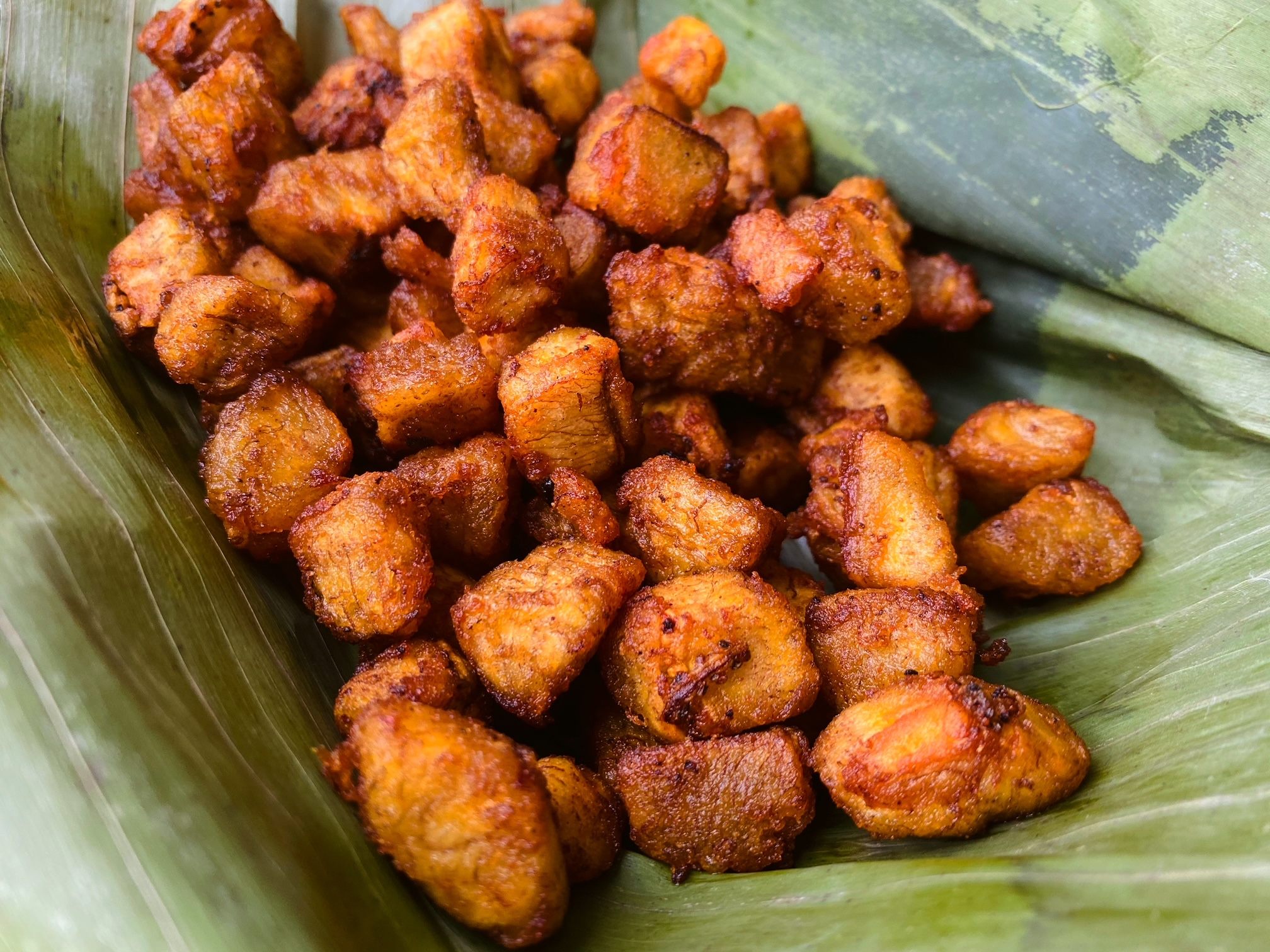 Fried brown chunks of plantains piled into a green banana leaf