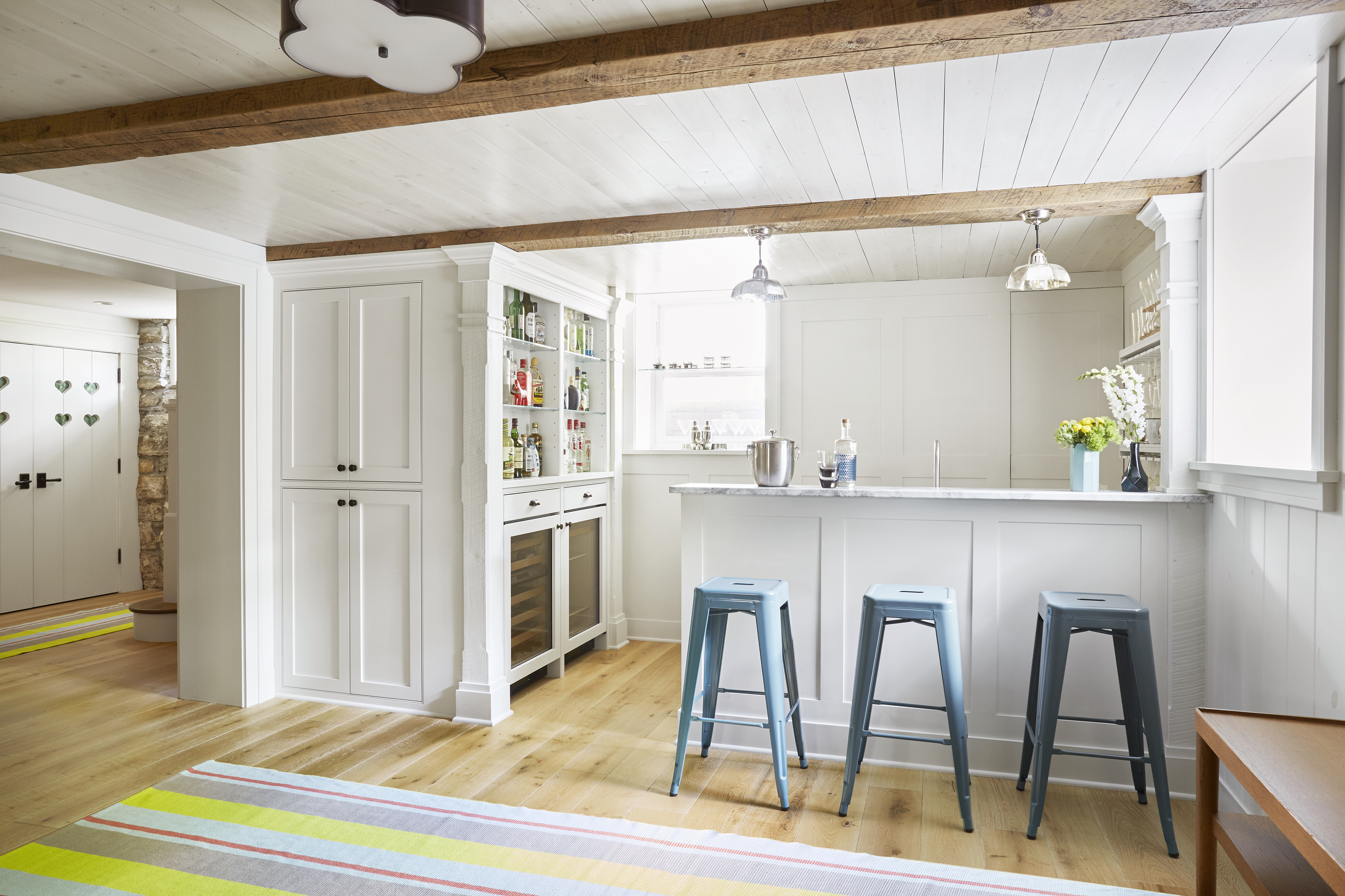 A basement kitchen with a breakfast bar and a painted wood plank ceiling.