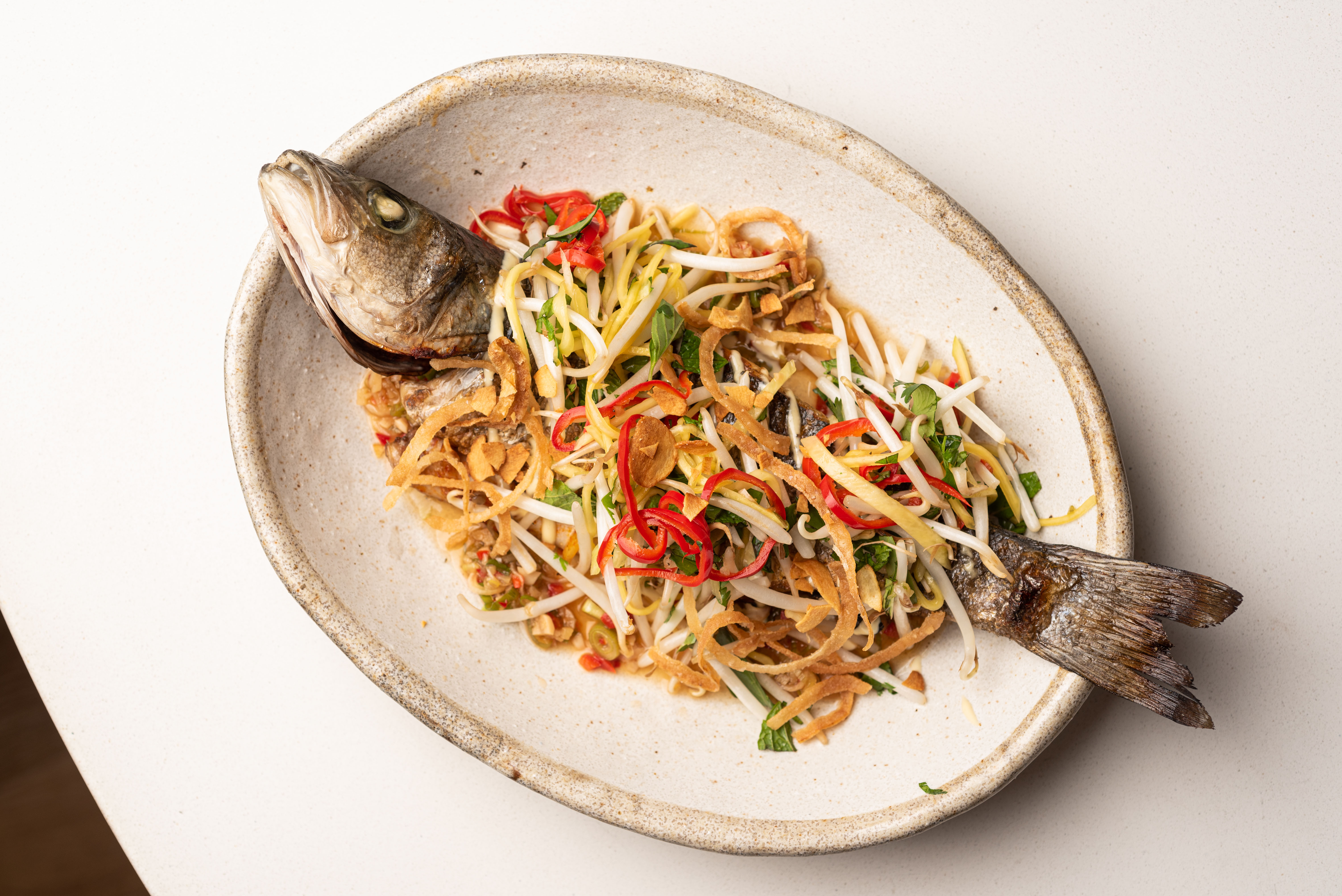 A whole cooked fish topped with shredded vegetables on a ceramic plate.