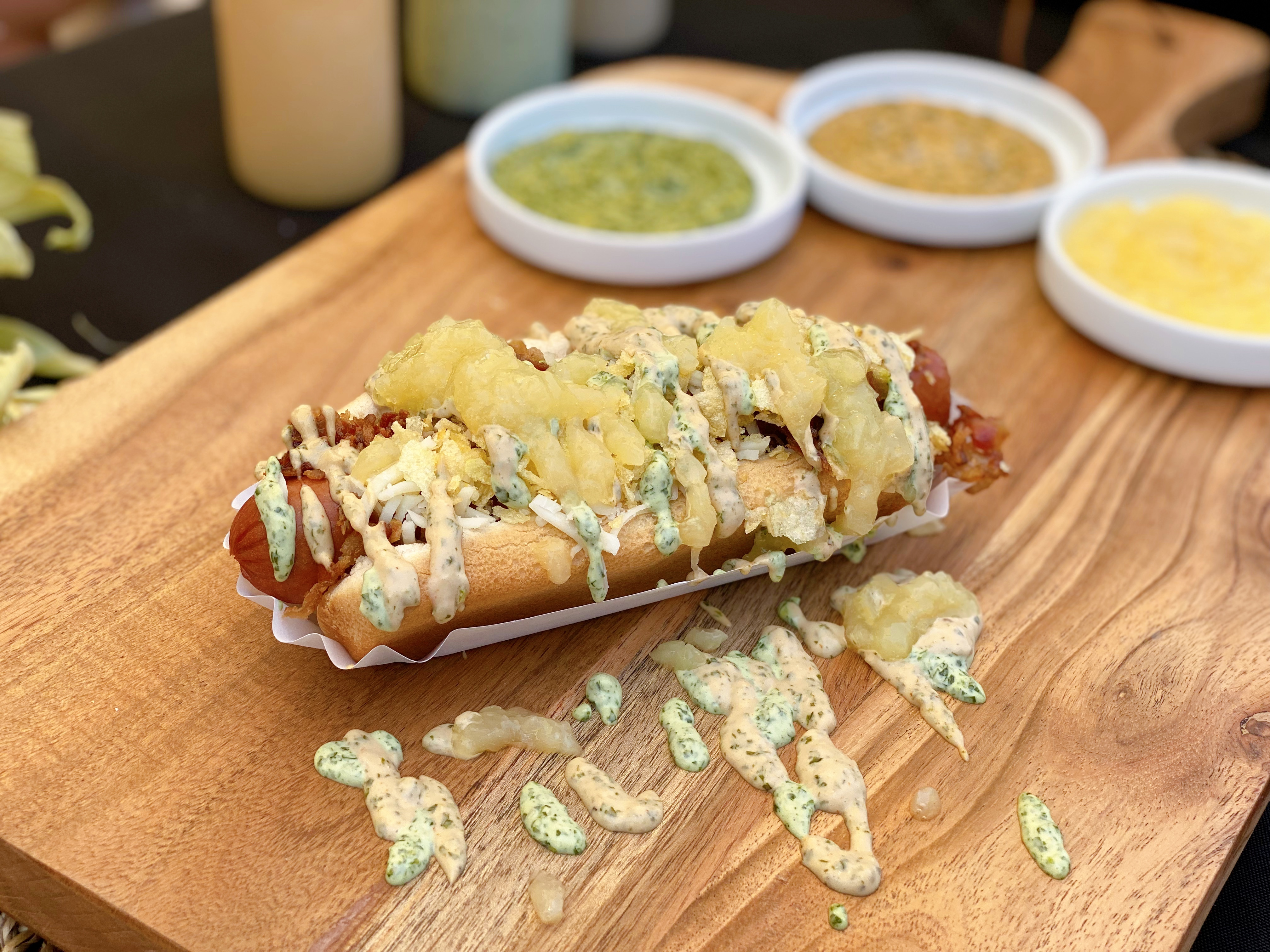 Colombian-style hot dog from WezzArepas sauced up on a wooden board.