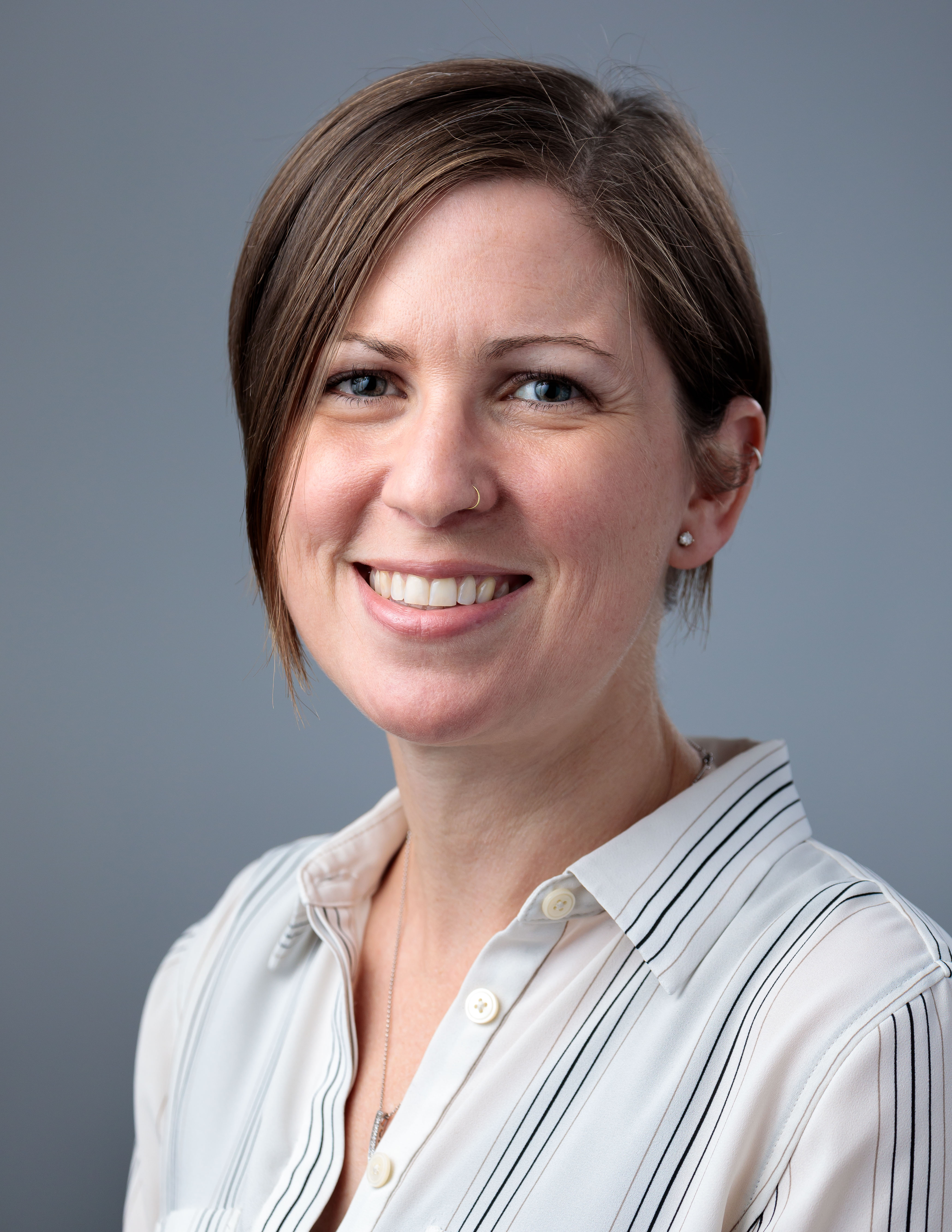 A researcher with short brown hair and a striped collared shirt poses for a headshot.