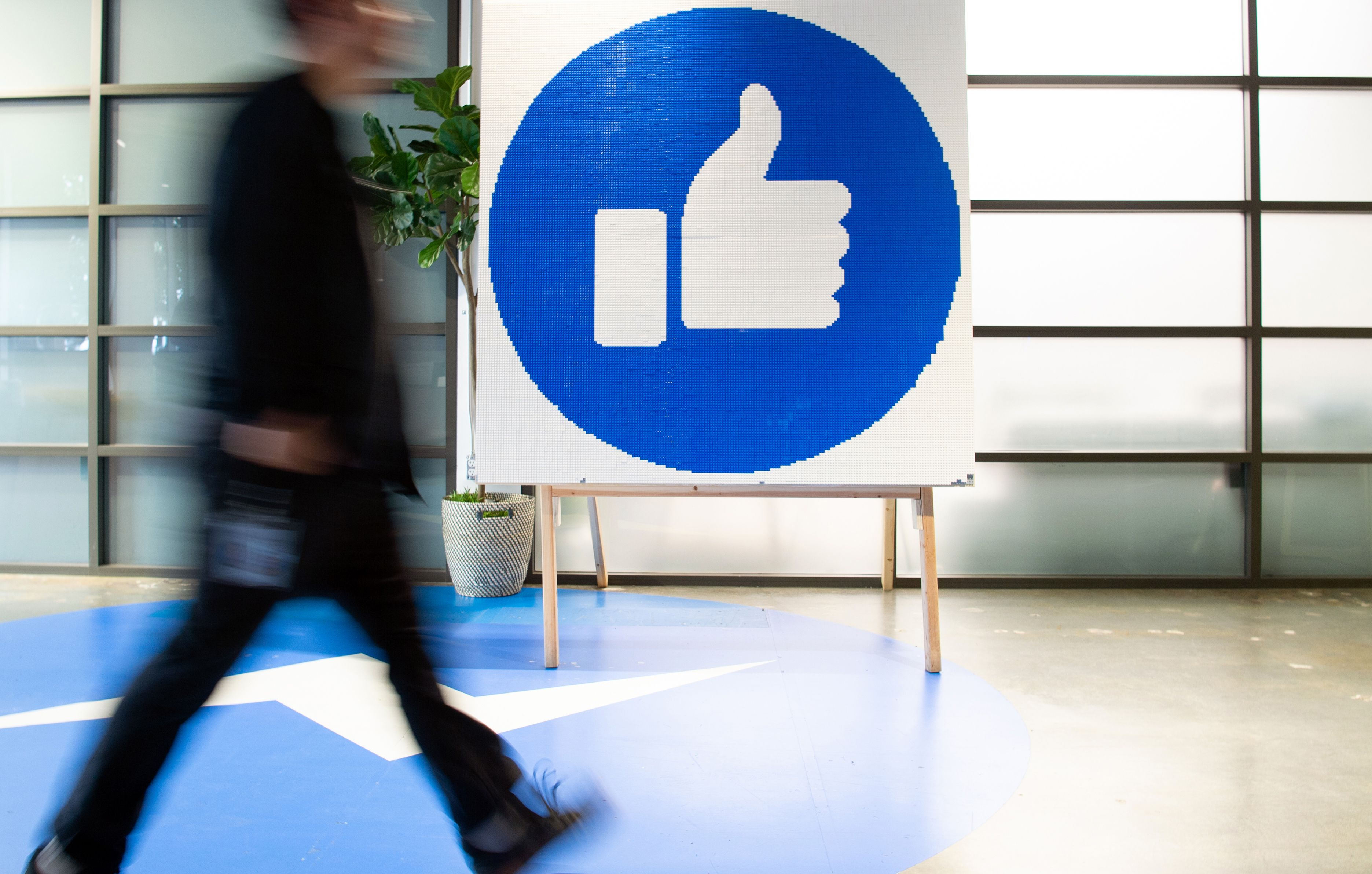 A blurry capture of a man walking past a large blue-and-white Facebook logo on display in a lobby.