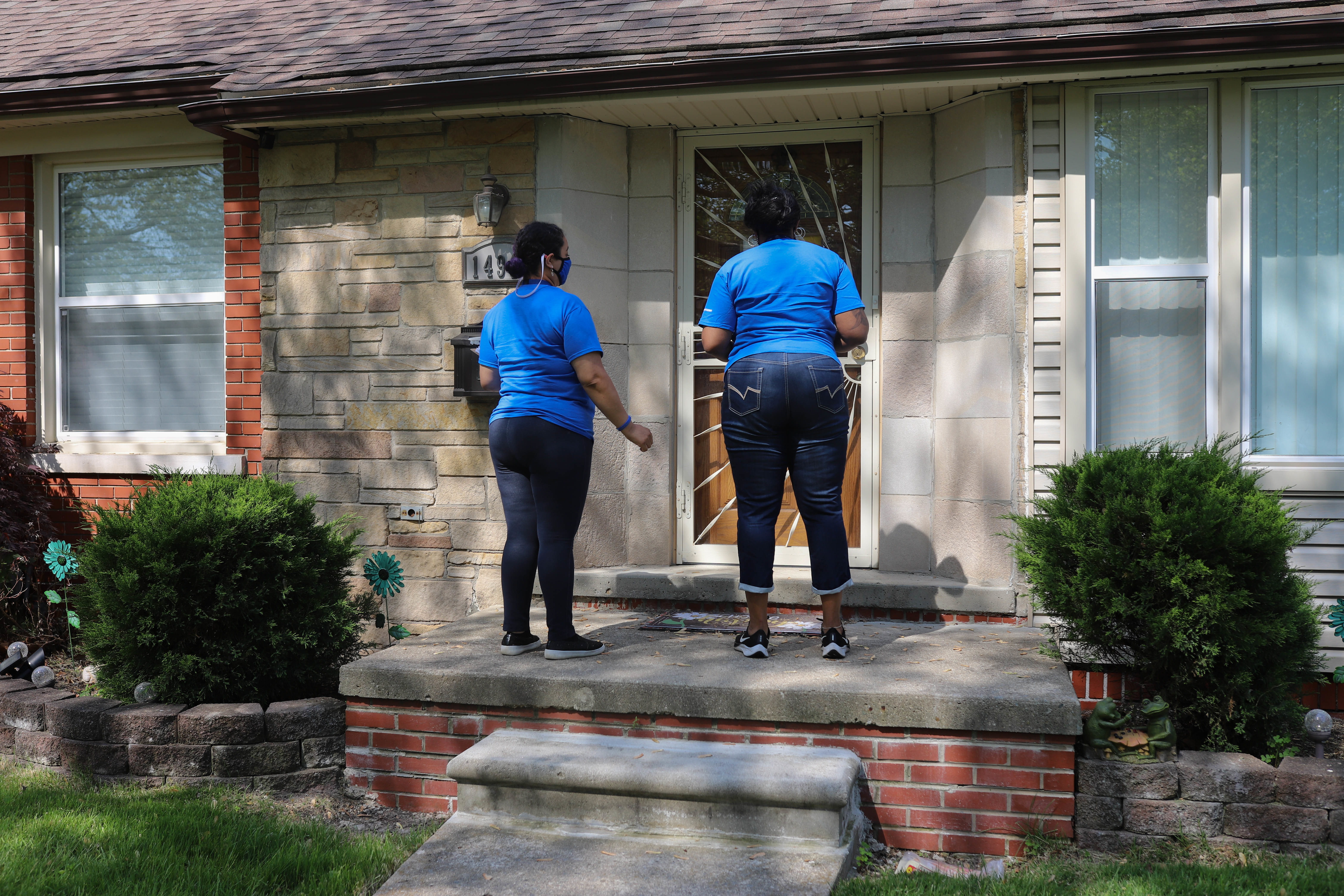 Two women, wearing blue shirts and jeans, stand at the front door of a house in Detroit, Mich. that is patterned from the sun and shadows.