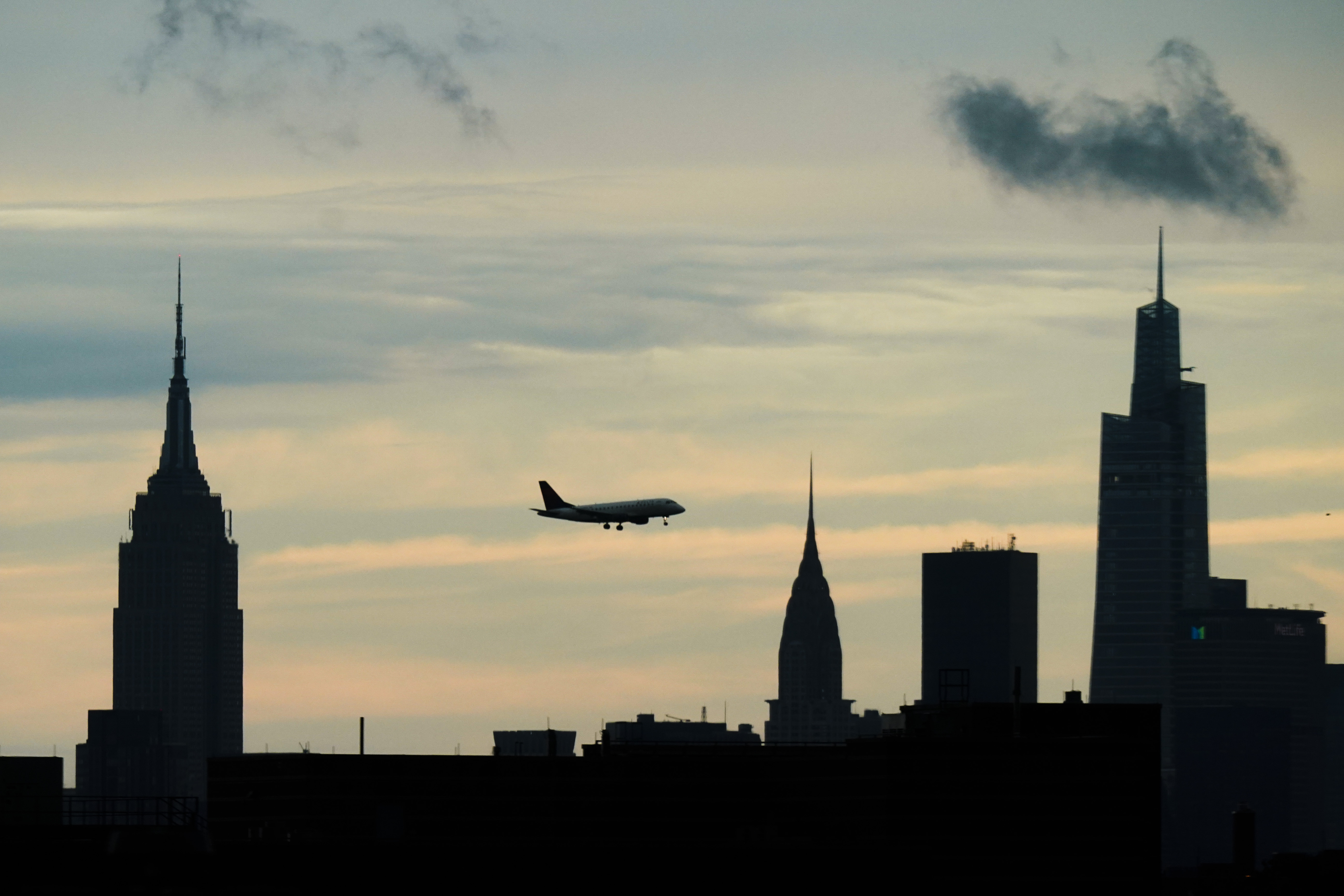 An airplane flies over the New York skyline in midtown Manhattan.