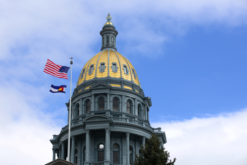 Colorado state Capitol building in Denver, Colorado , with the U.S. and state flags in front of a cloudy sky