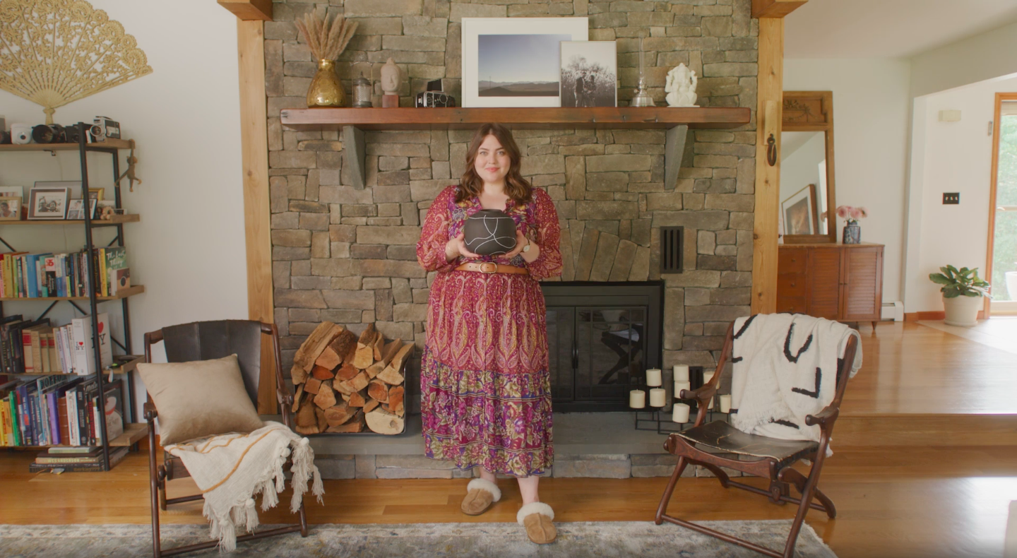 A woman wearing a patterned dress standing in front of a fireplace, holding a decorative vase.