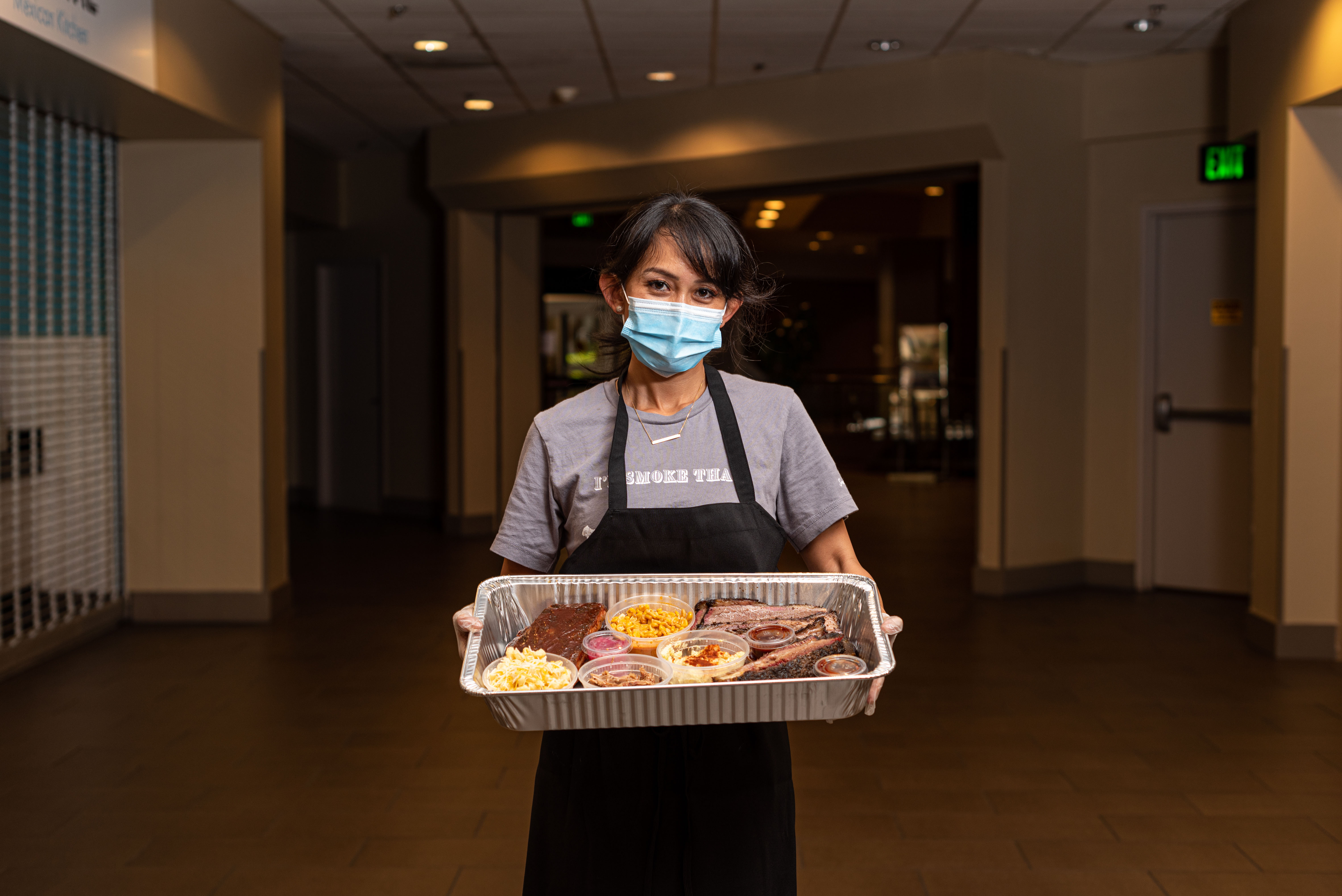 A woman in a mask holding a large silver tray of barbecue and sides.