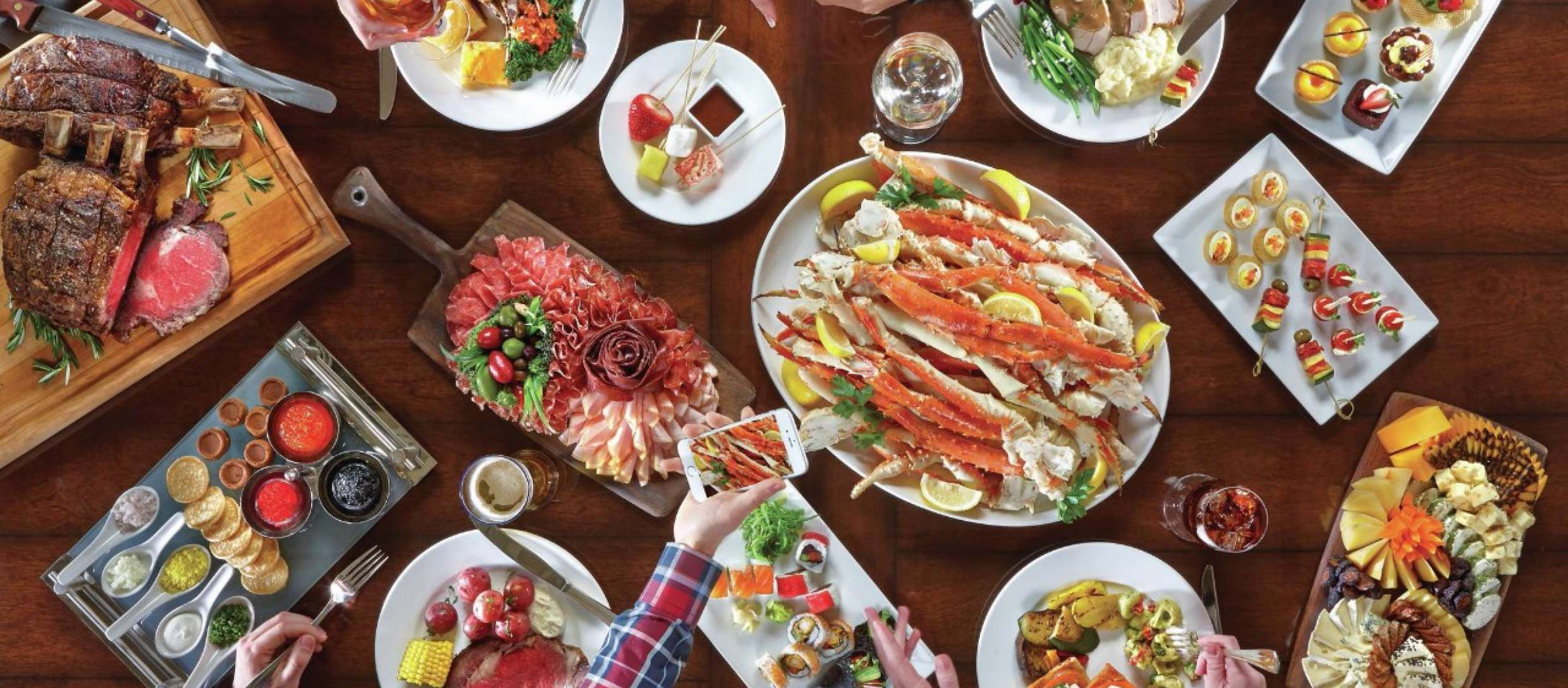 An overhead shot of crab legs, charcuterie, and more dishes
