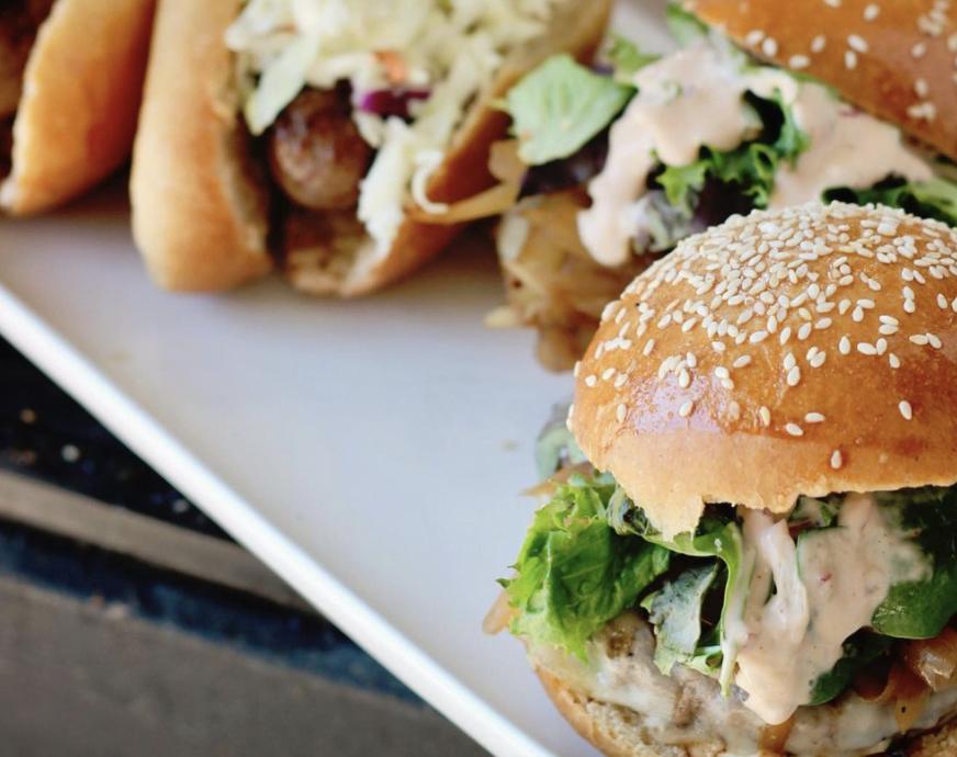 一个特写镜头,一个汉堡放在一个有种子的小面包上,背景是面包上的香肠