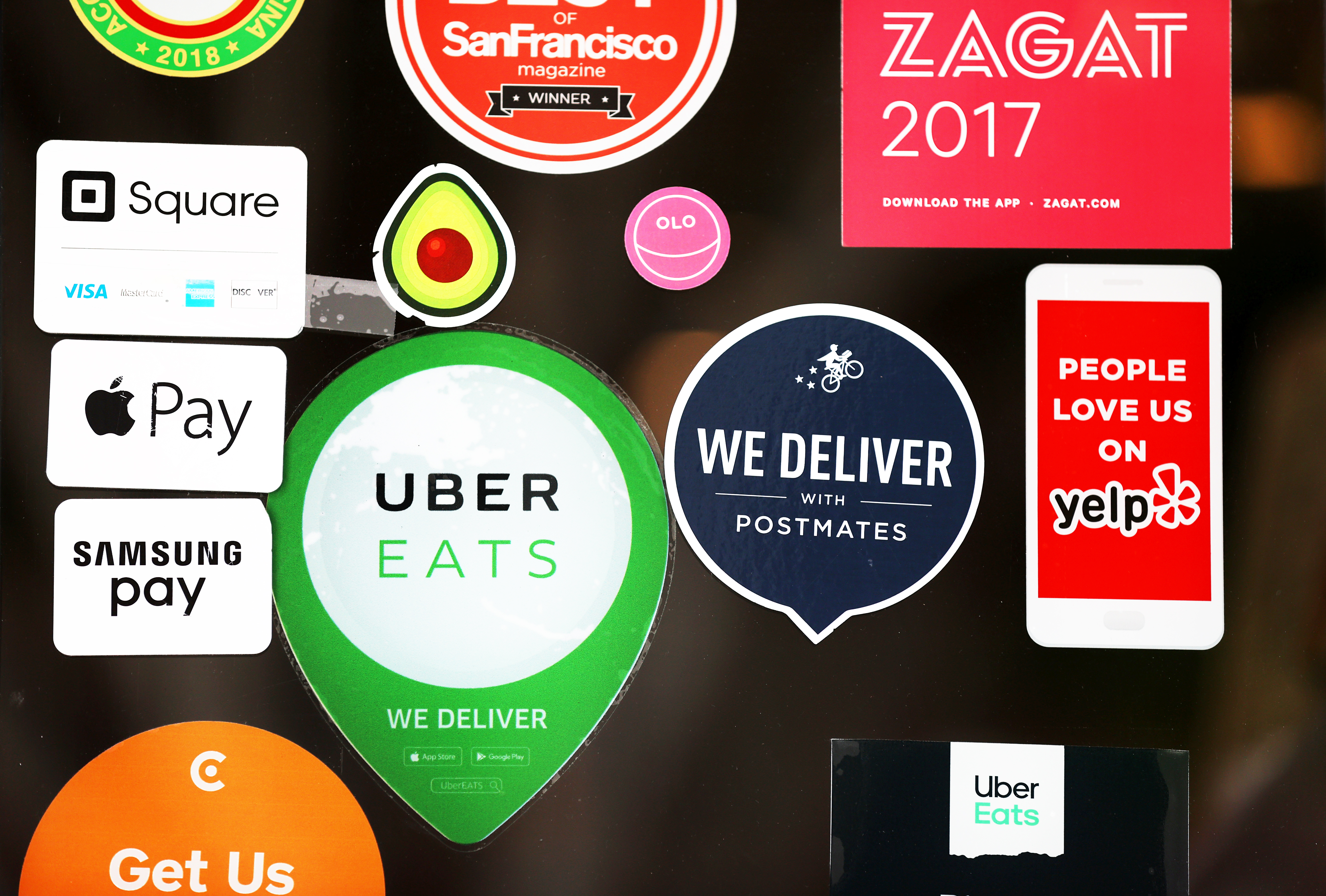 Stickers on a restaurant window for various delivery options.