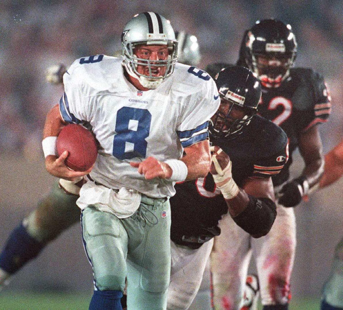 Dallas Cowboys quarterback Troy Aikman scrambles o