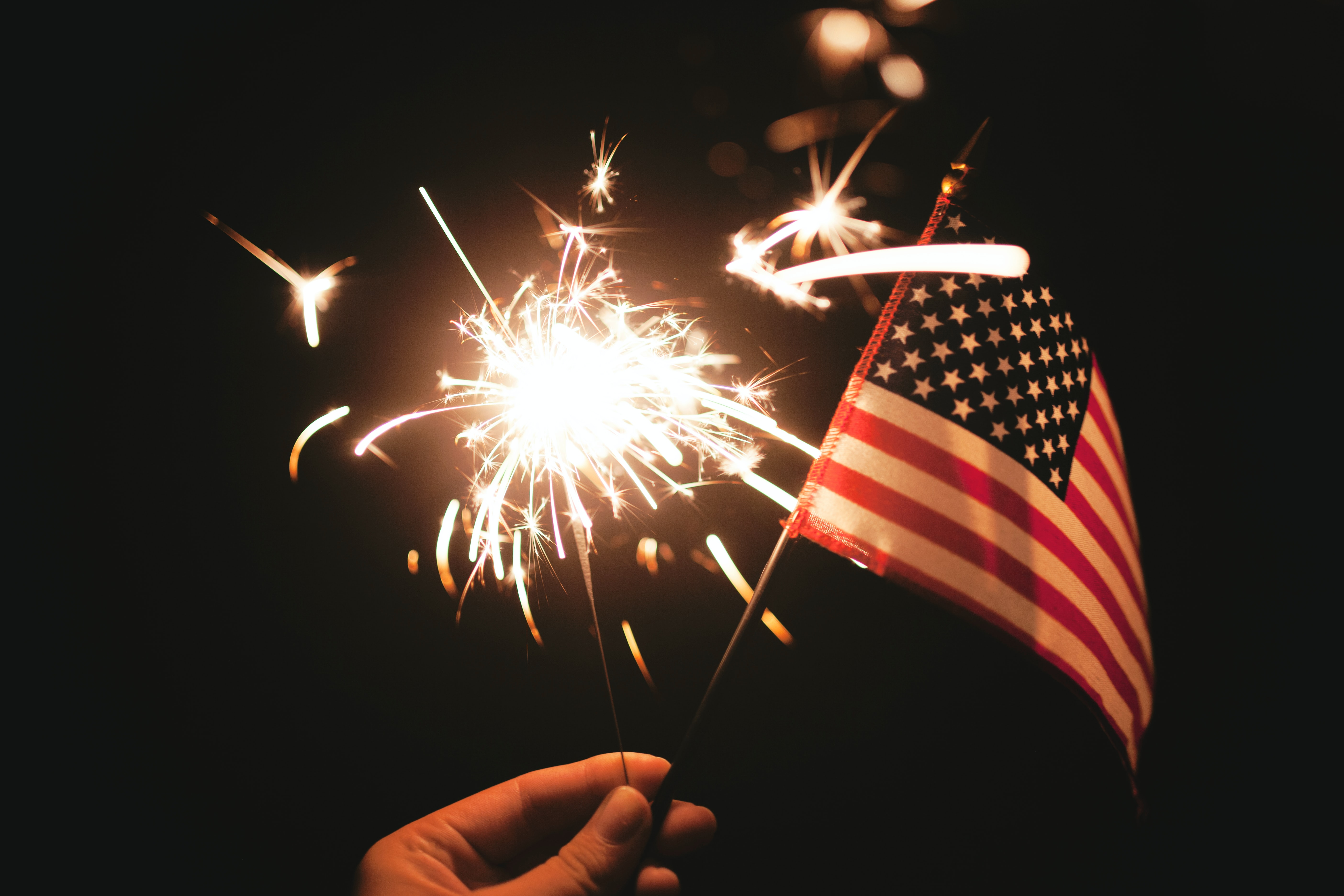 hand holding a sparkler and flag against the night background