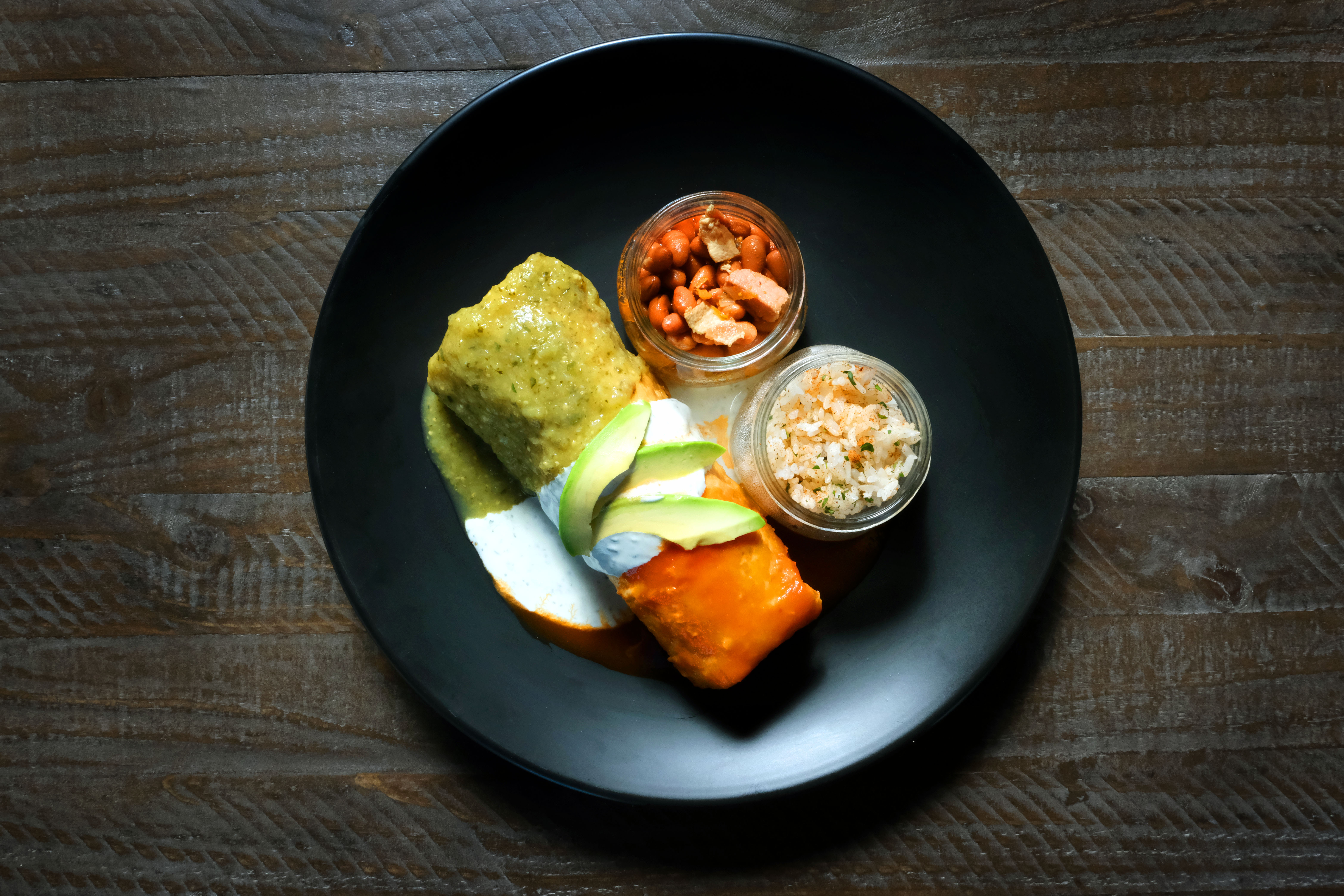 Triple threat chimichanga with green, white, and red sauces