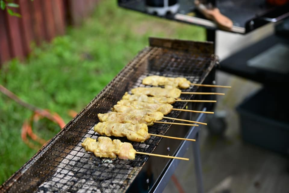 a bunch of skewered meat being cooked on an outdoor grill