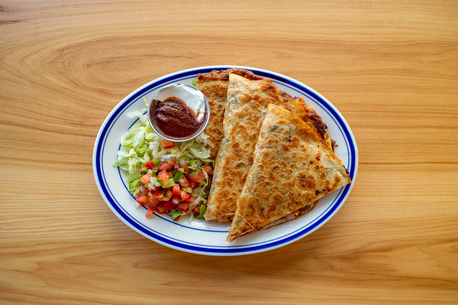 A blistery quesadilla with a small side salad and bowl of salsa and sour cream.