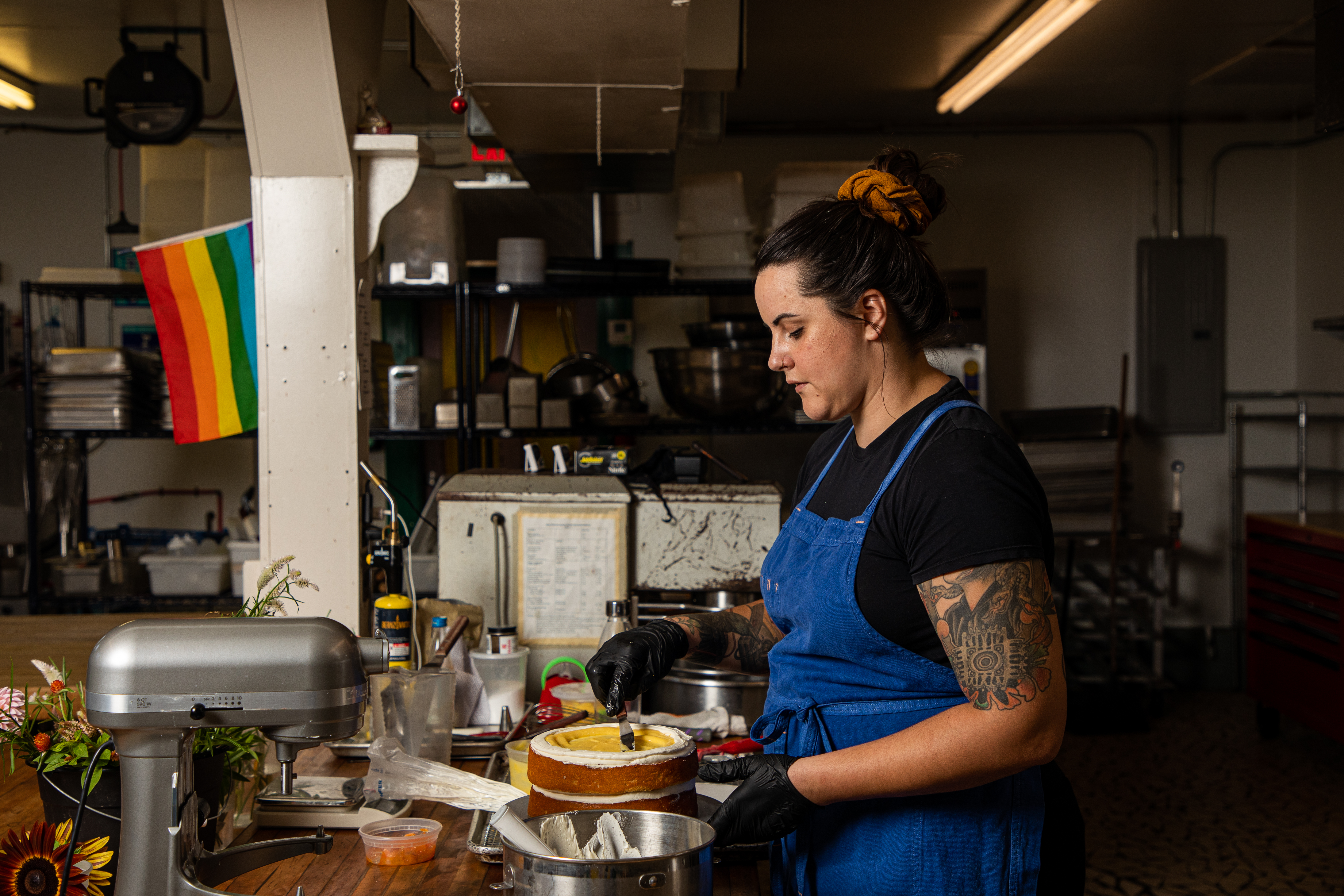A woman in a black shirt and blue apron ices a cake in a commercial kitchen with a Pride flag in the background