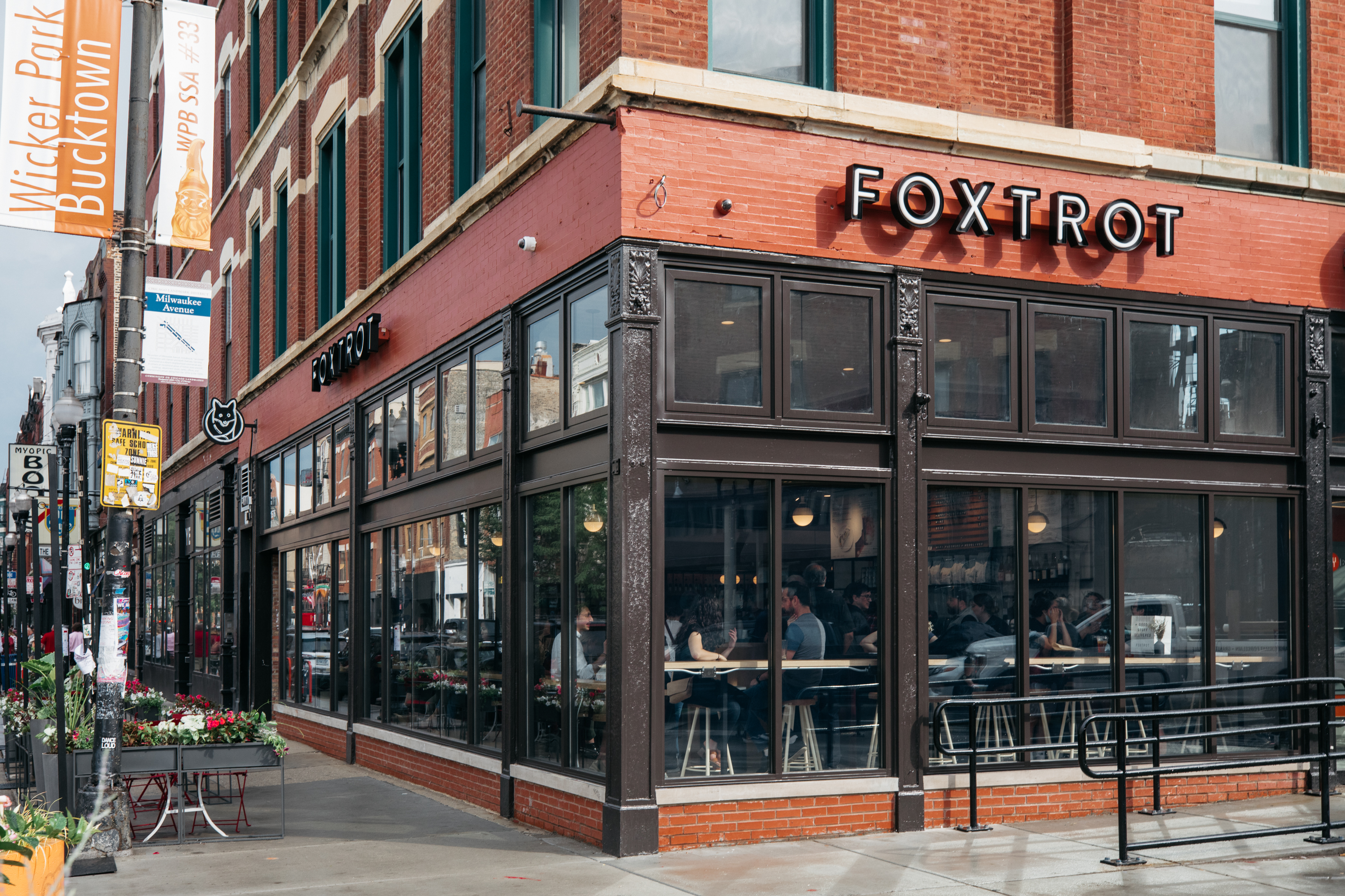 """A large brick corner building with a sign that reads """"Foxtrot"""""""