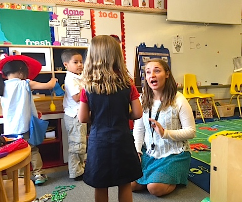 A preschool teacher sitting on the floor talks with one of her students, who is facing her.