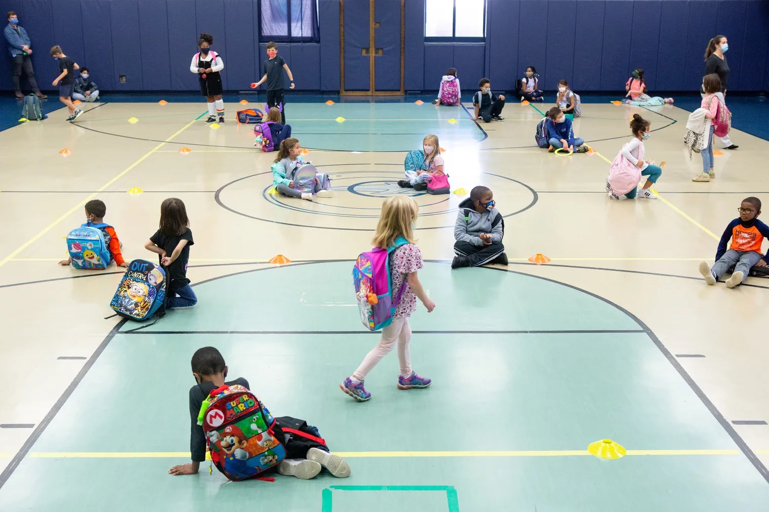 Several young elementary students are social distanced in a school gymnasium.