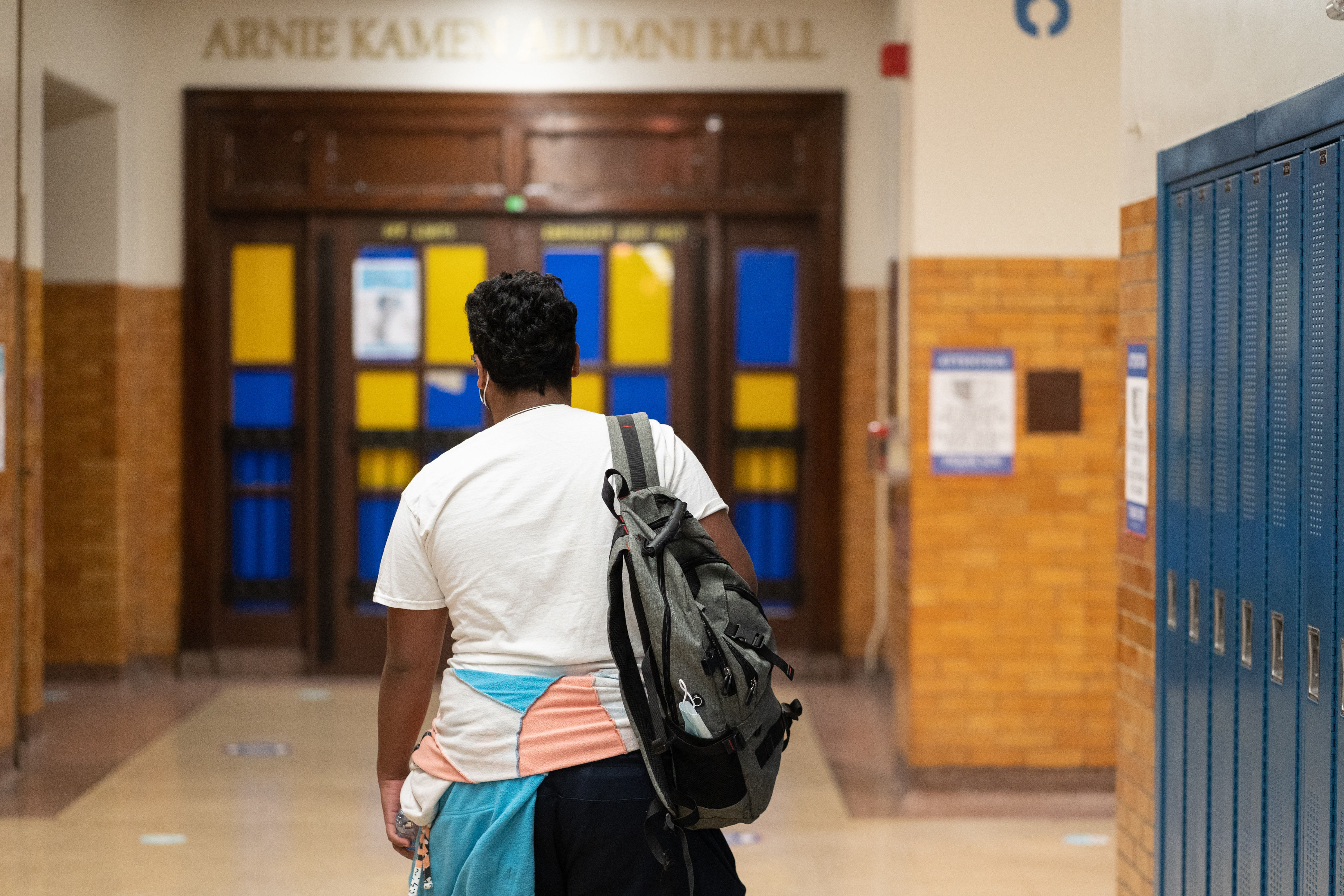 A young man walks through a school hallways, wearing a backpack, white shirt, and blue, pink, and white windbreaker tied around his waist.