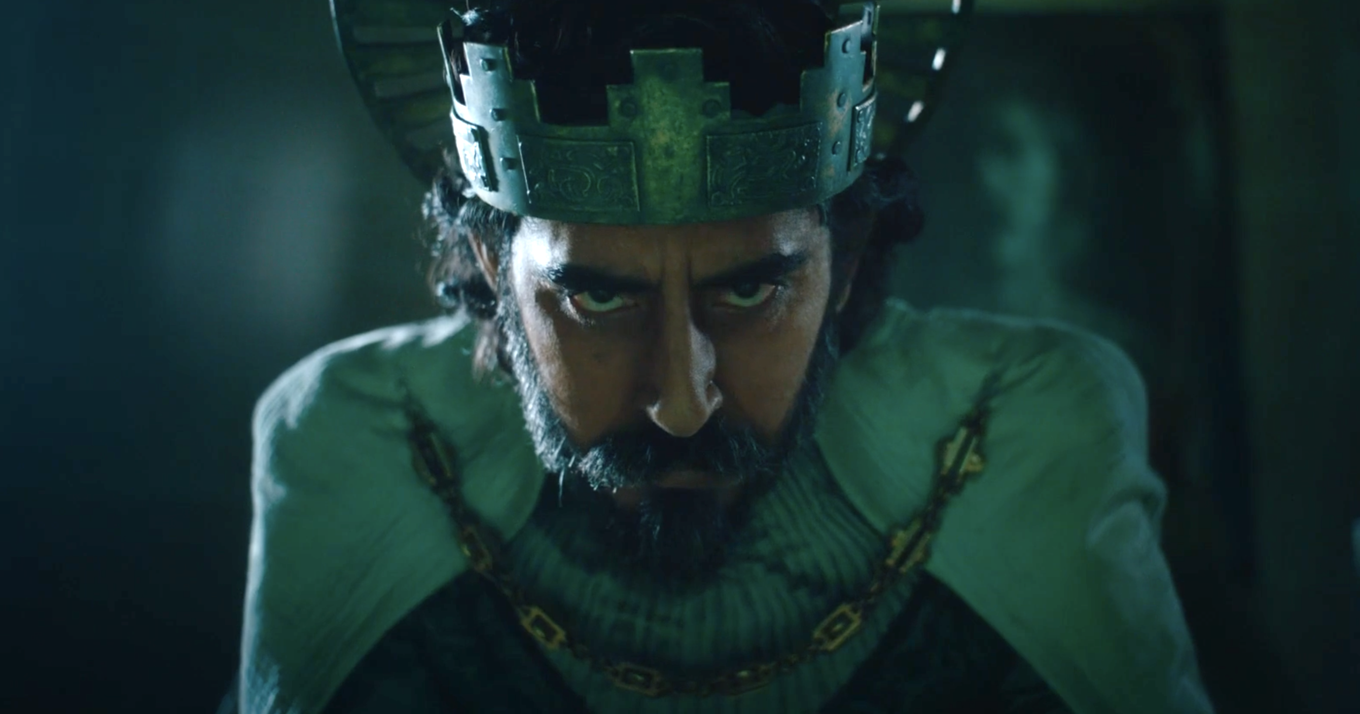 Dev Patel wears robes and a crown, and a pained expression.