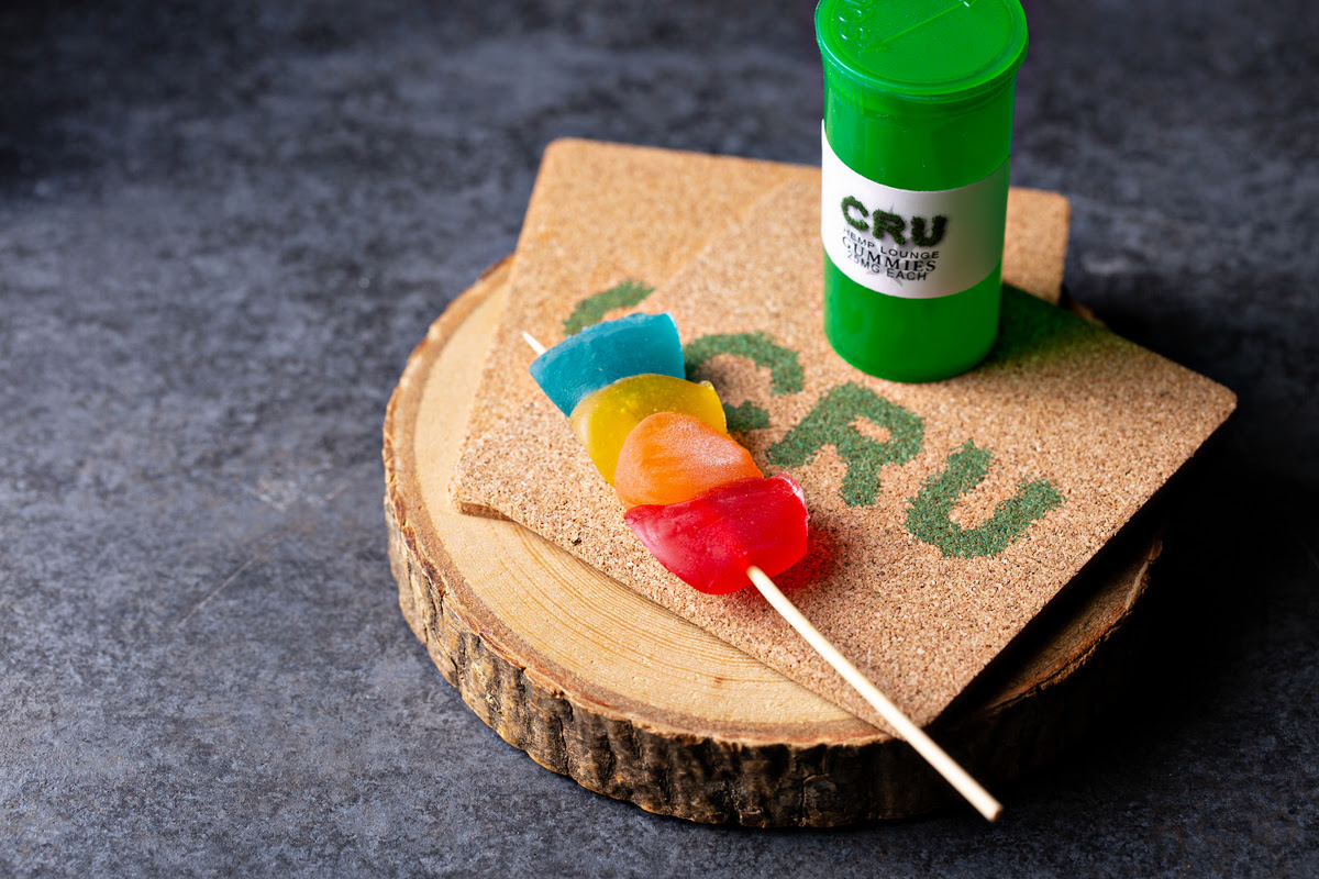 """Blue, yellow, and red gummy candies infused with CBD on a paper skewer. The candies sit atop a wood trivet emblazoned with """"CRU"""""""
