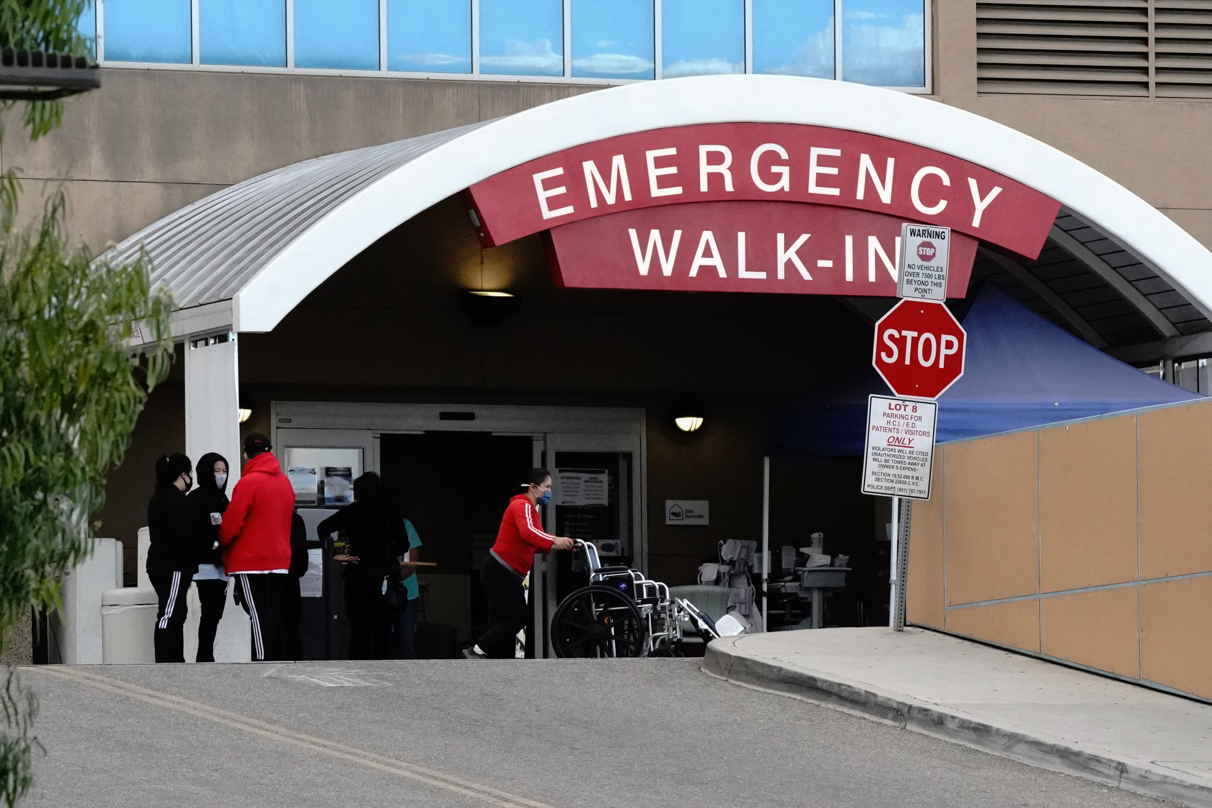 People stand outside the emergency room at Riverside Community Hospital in Riverside, California.