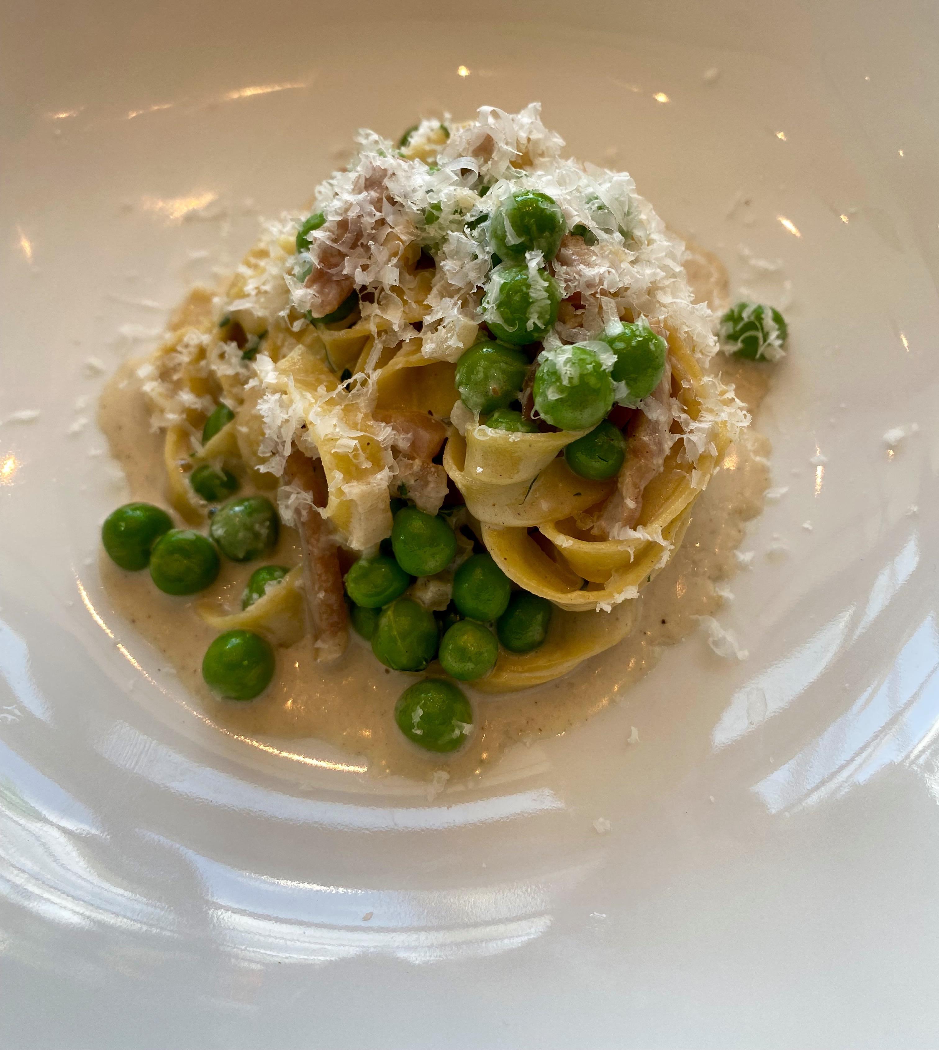 Tagliolini with prosciutto and peas tossed in porcini cream