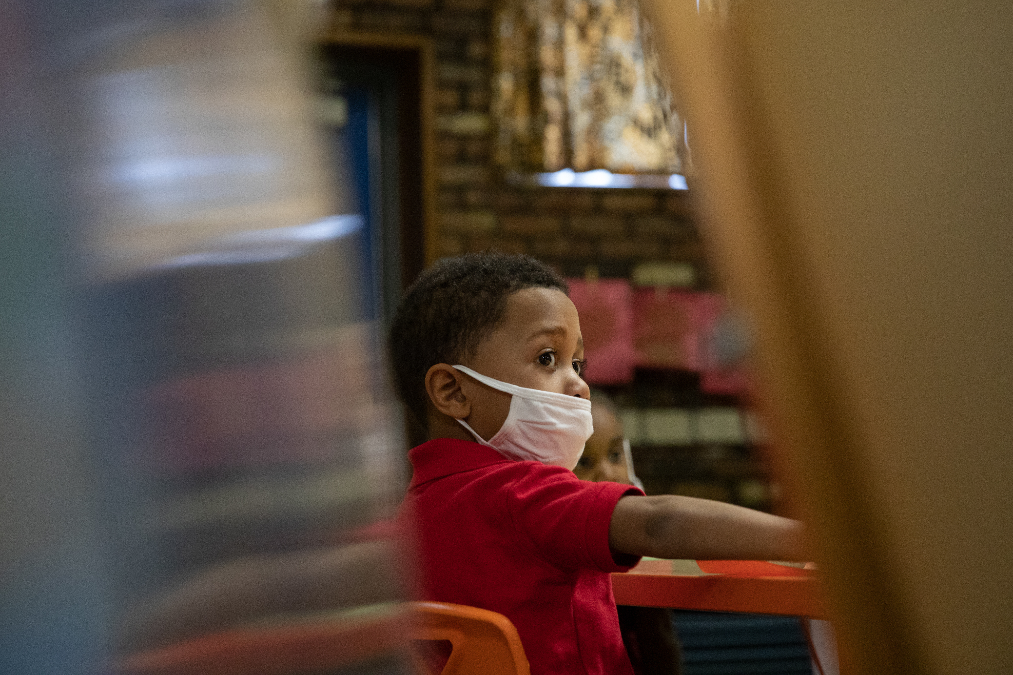 A preschooler listens to instructions for a painting activity during a preschool class at Little Scholars child care center.