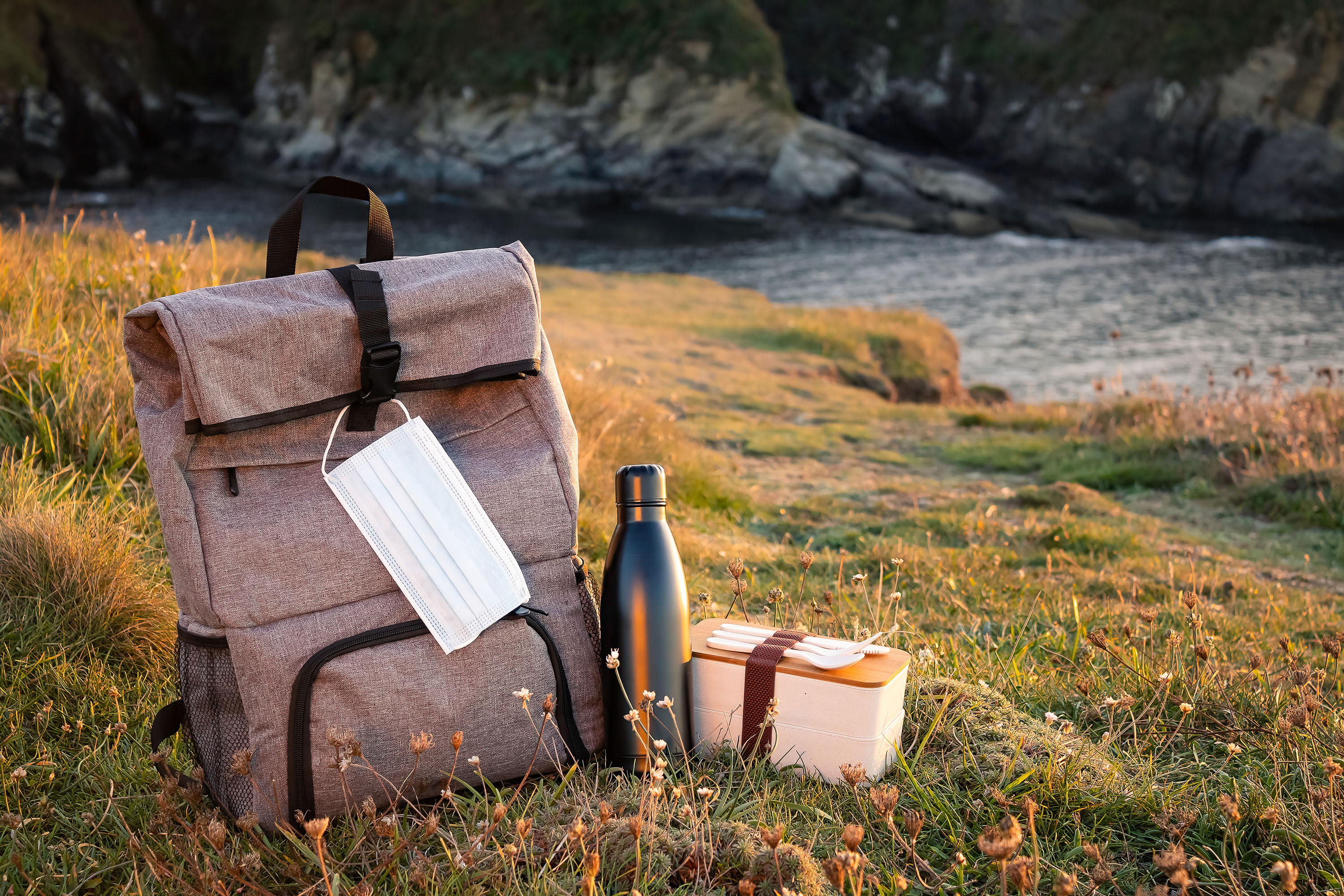 A hiking backpack, reuseable water bottle, and bento box in a meadow with a body of water in the background.